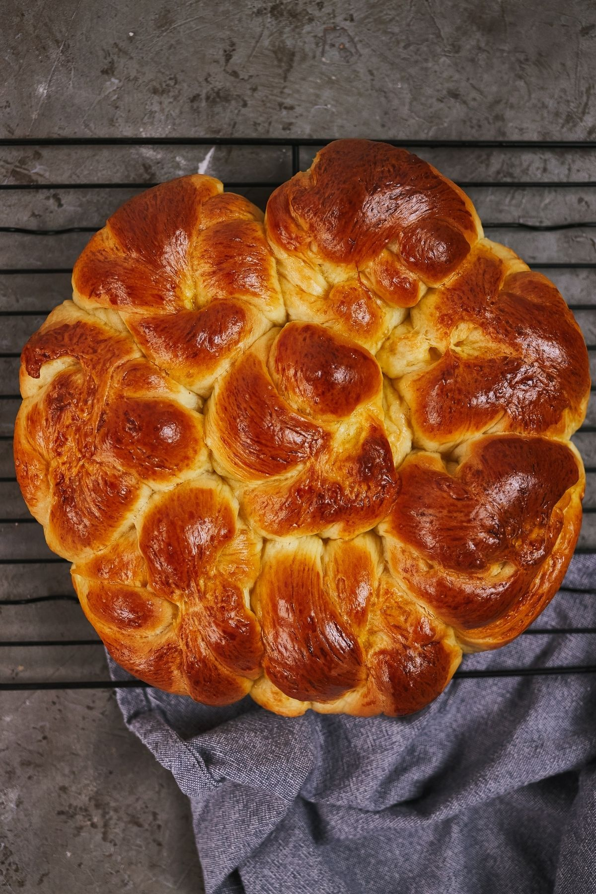 Pan of browned milk bread knot rolls on top of black wire rack over gray table