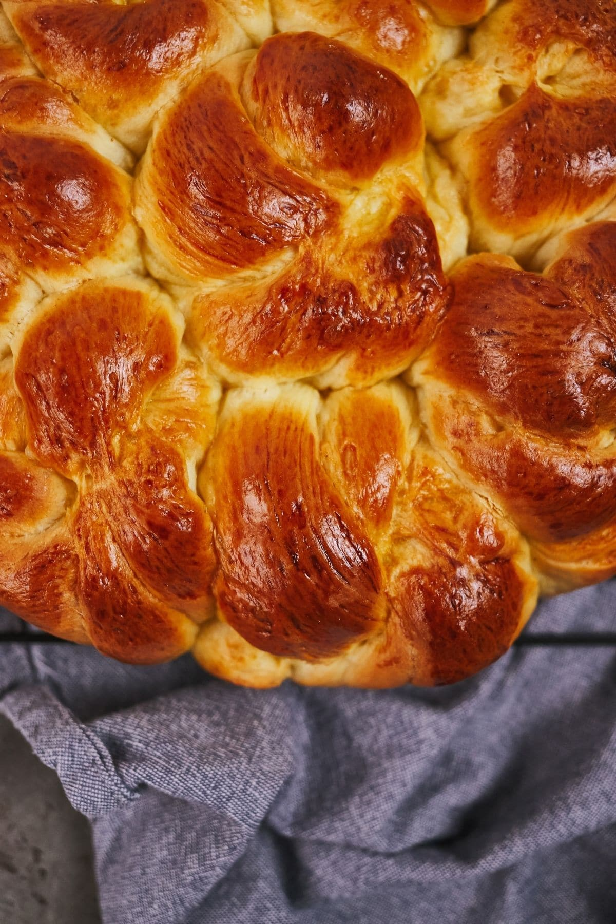 browned bread rolls on top of rack over blue napkin