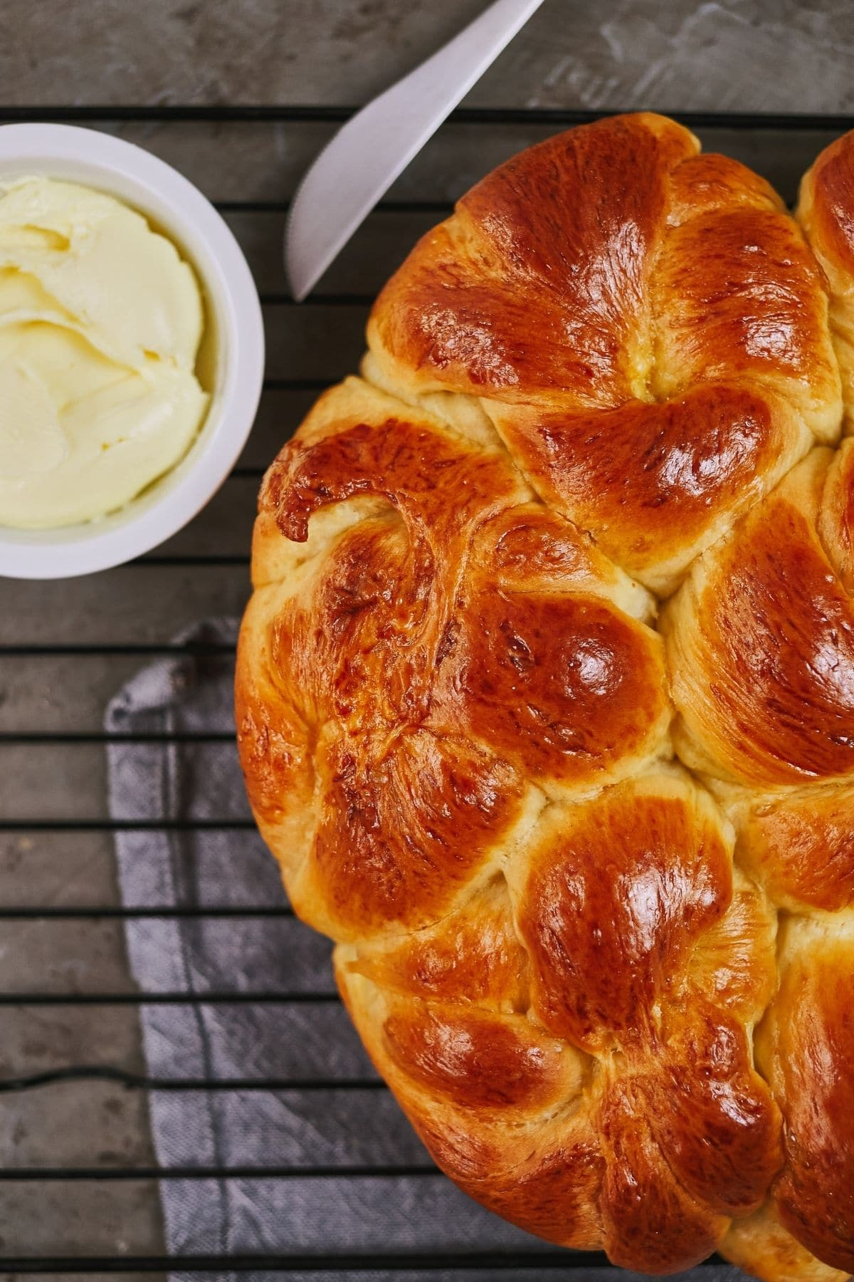 over head image of pan of hot rolls on rack by bowl of butter