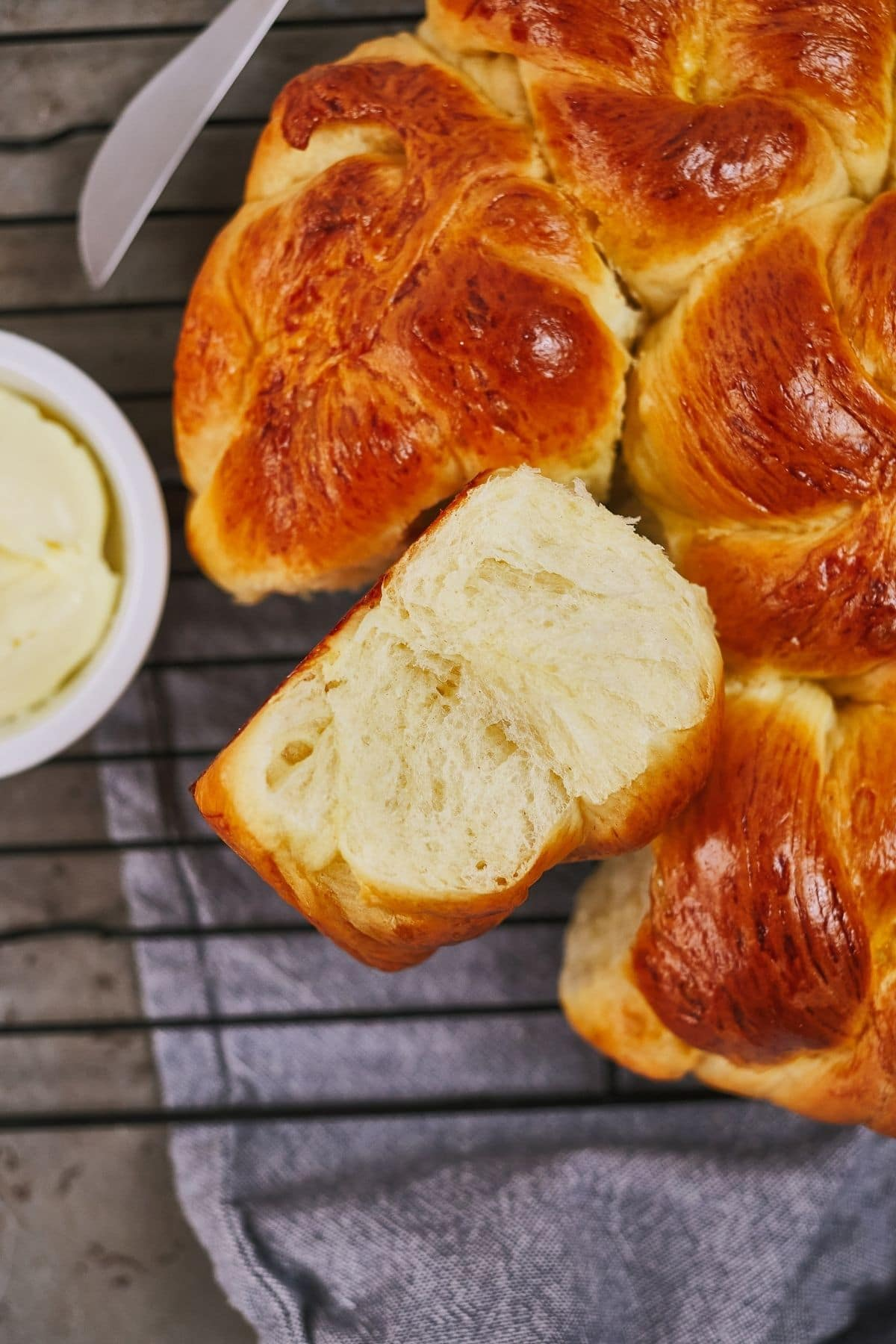 hot rolls with one on its side next to bowl of butter on wire rack
