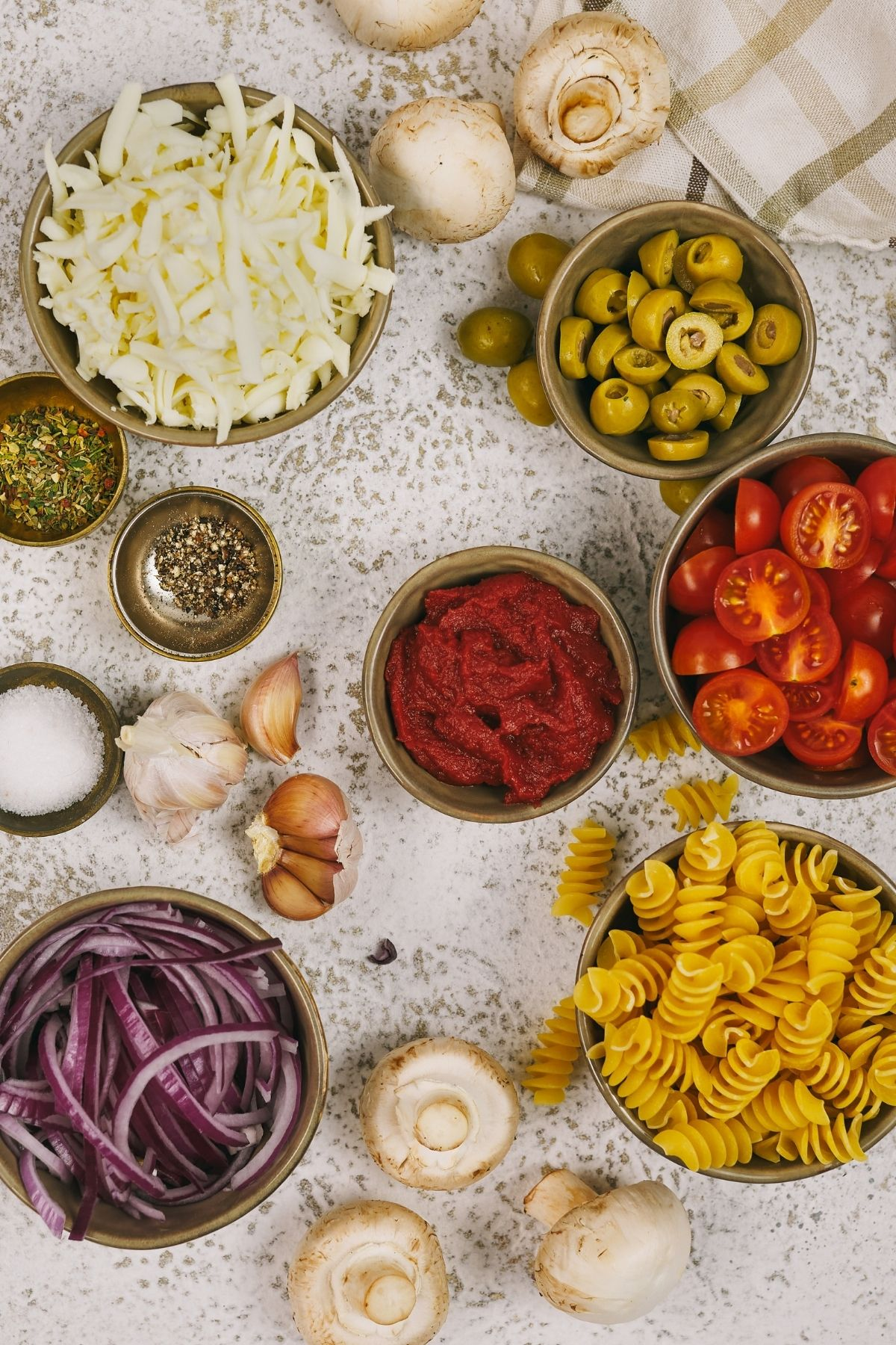 Ingredients for pasta in bowls on marble table