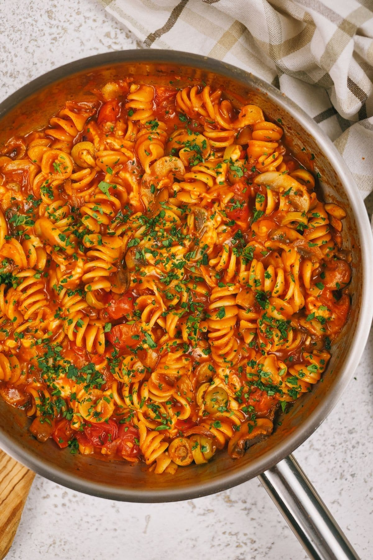 Skillet of rotini with tomato sauce on marble table