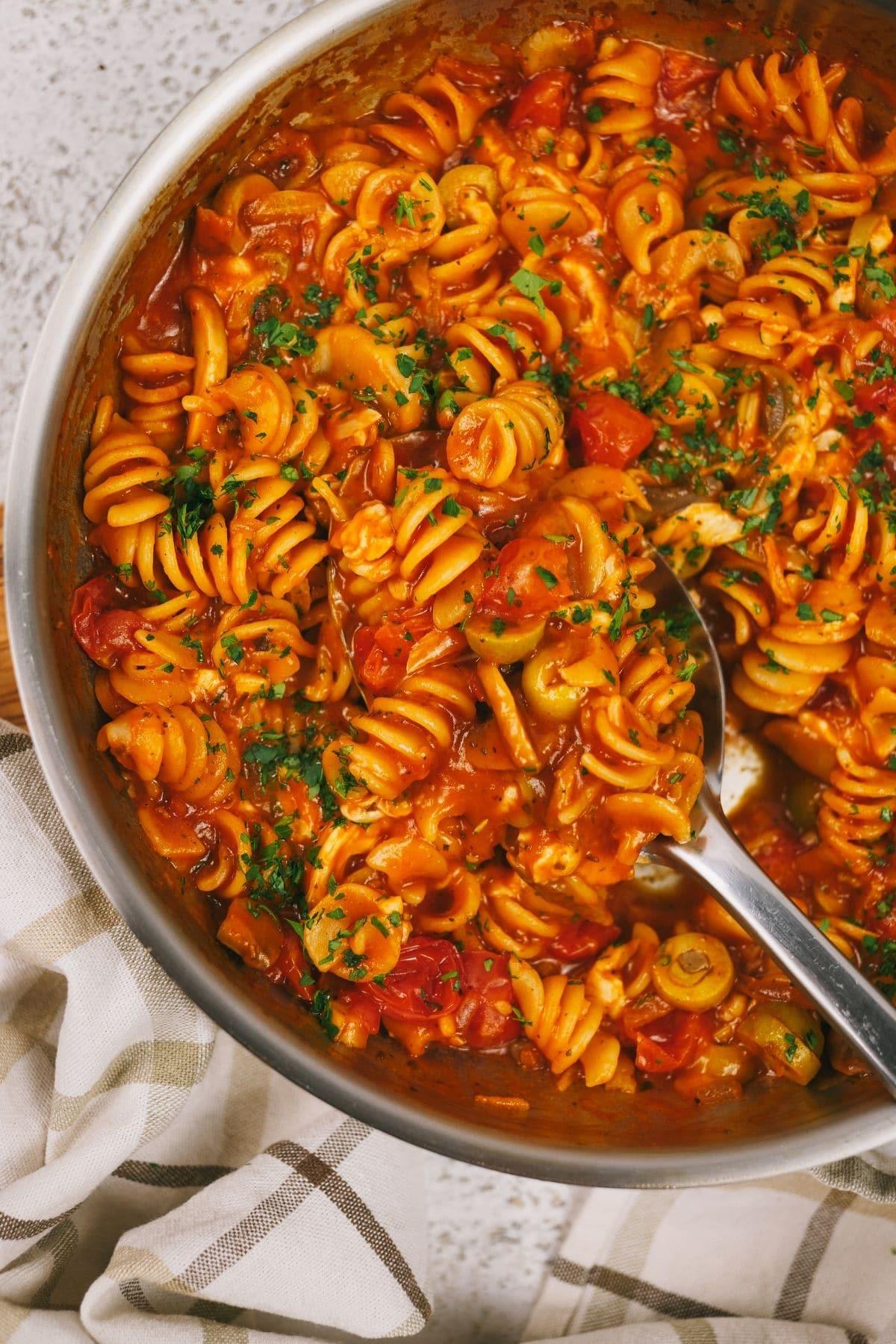 Metal spoon in skillet of tomato pasta