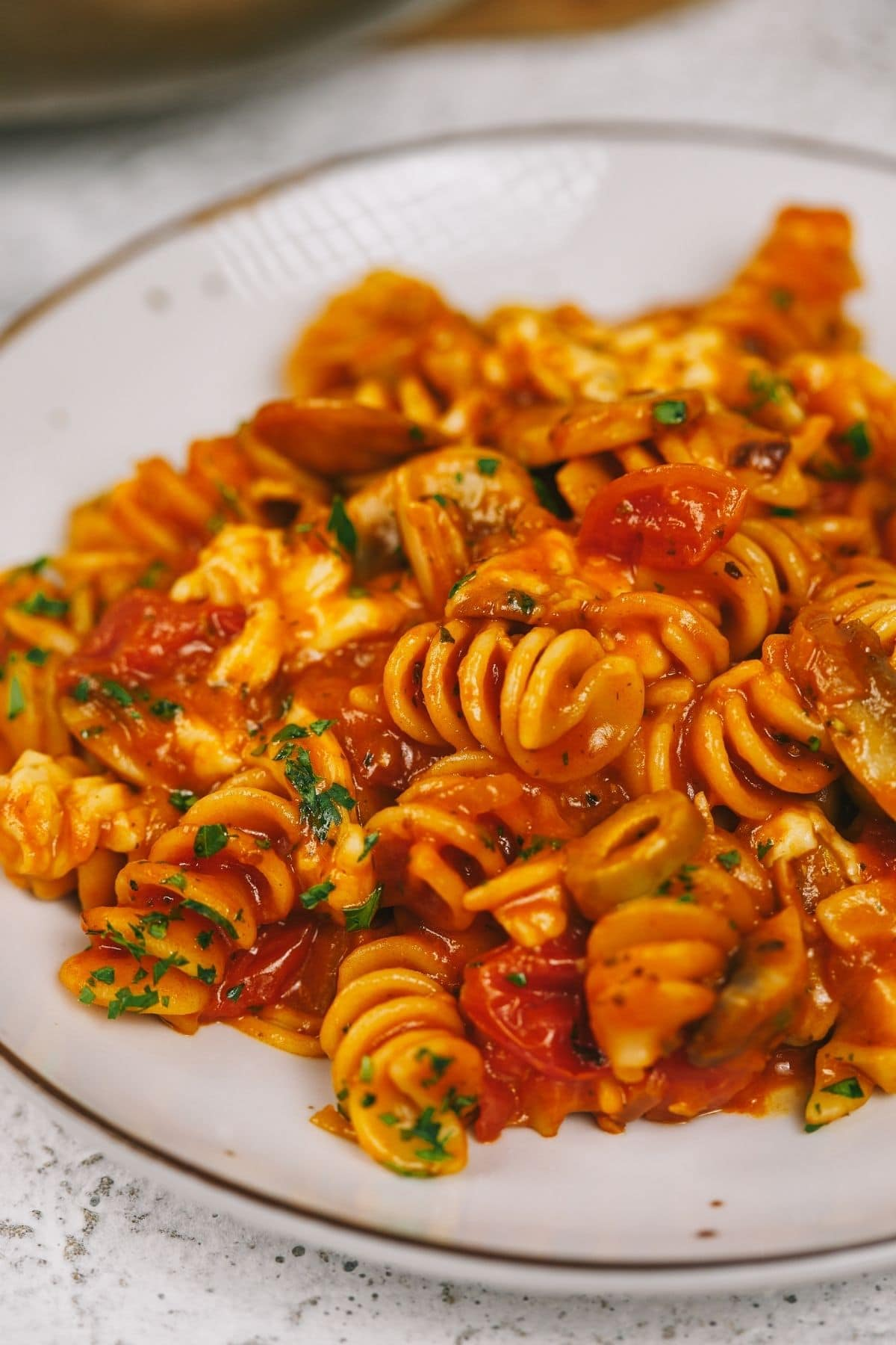 White and brown plate filled with pasta and vegetables in tomato sauce