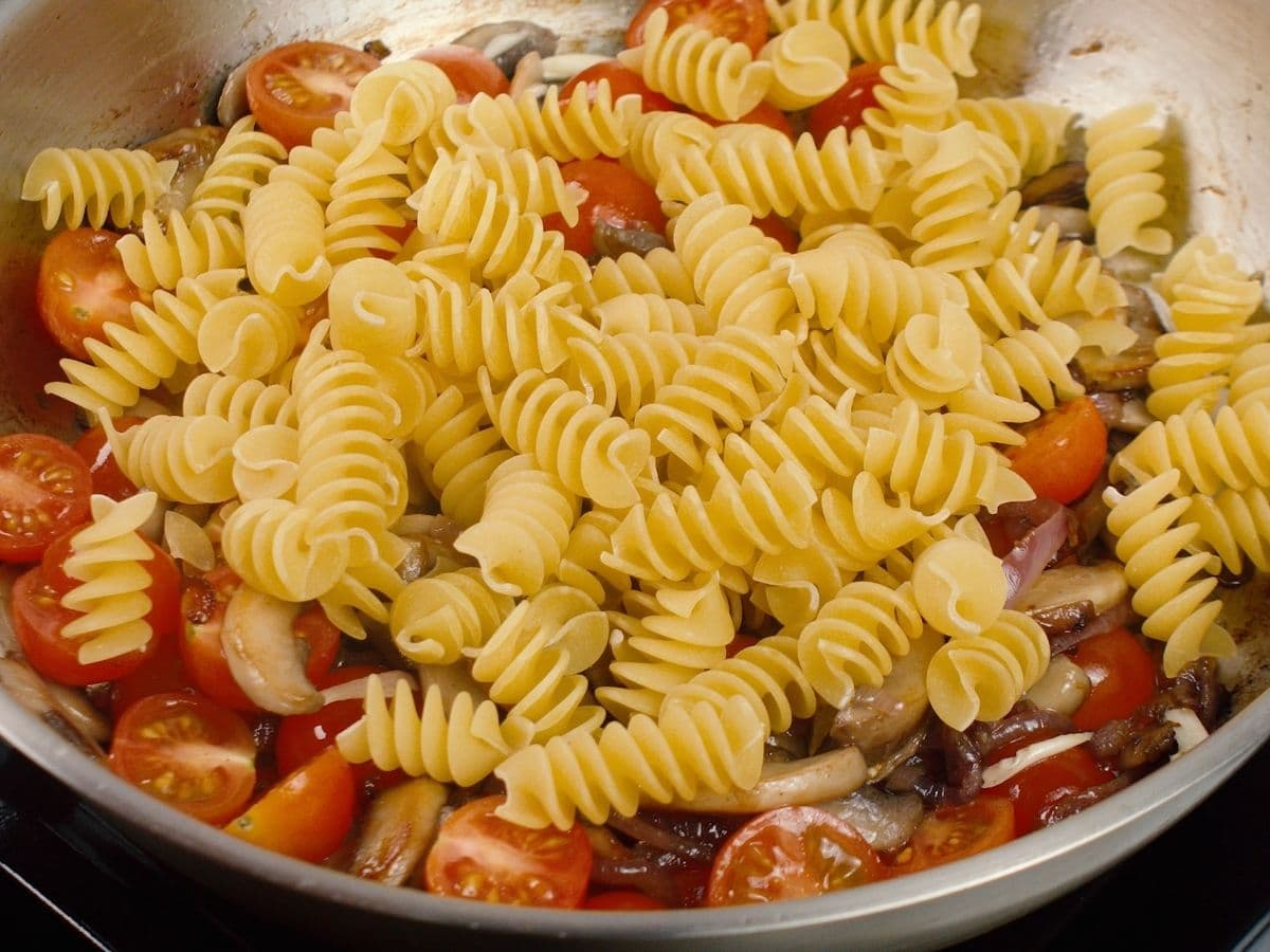Raw pasta on top of tomatoes and mushrooms in skillet