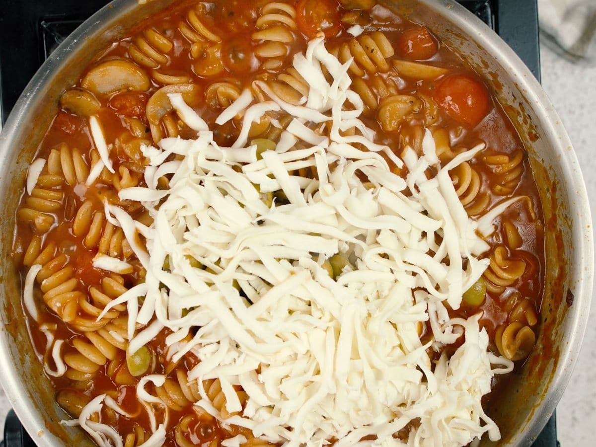 Shredded cheese on top of cooked tomato pasta