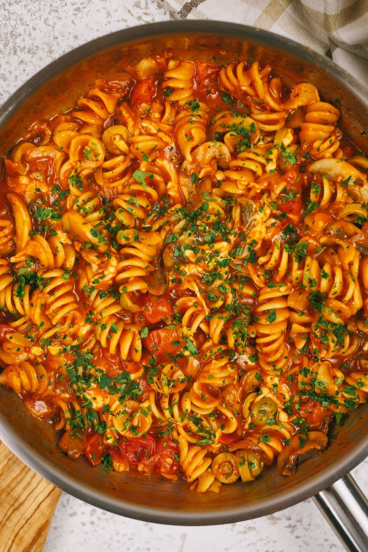 Large skillet of one pot pasta topped with parsley