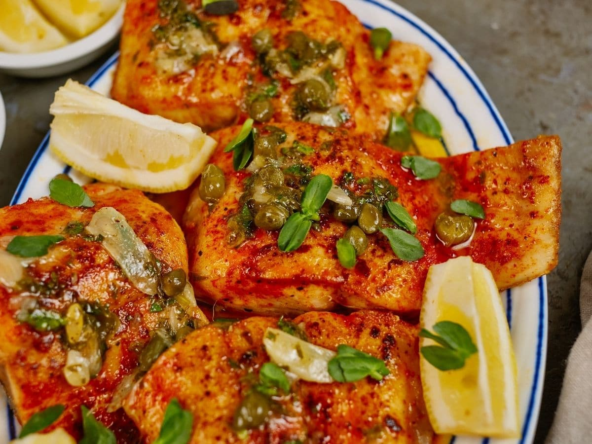 white plate of fish with herbs and lemon on top