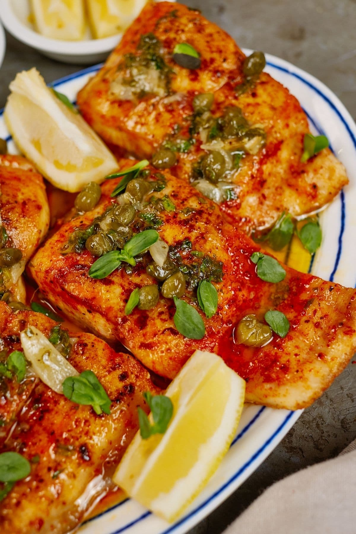perpared pan seared halibut on plate with lemon and herbs