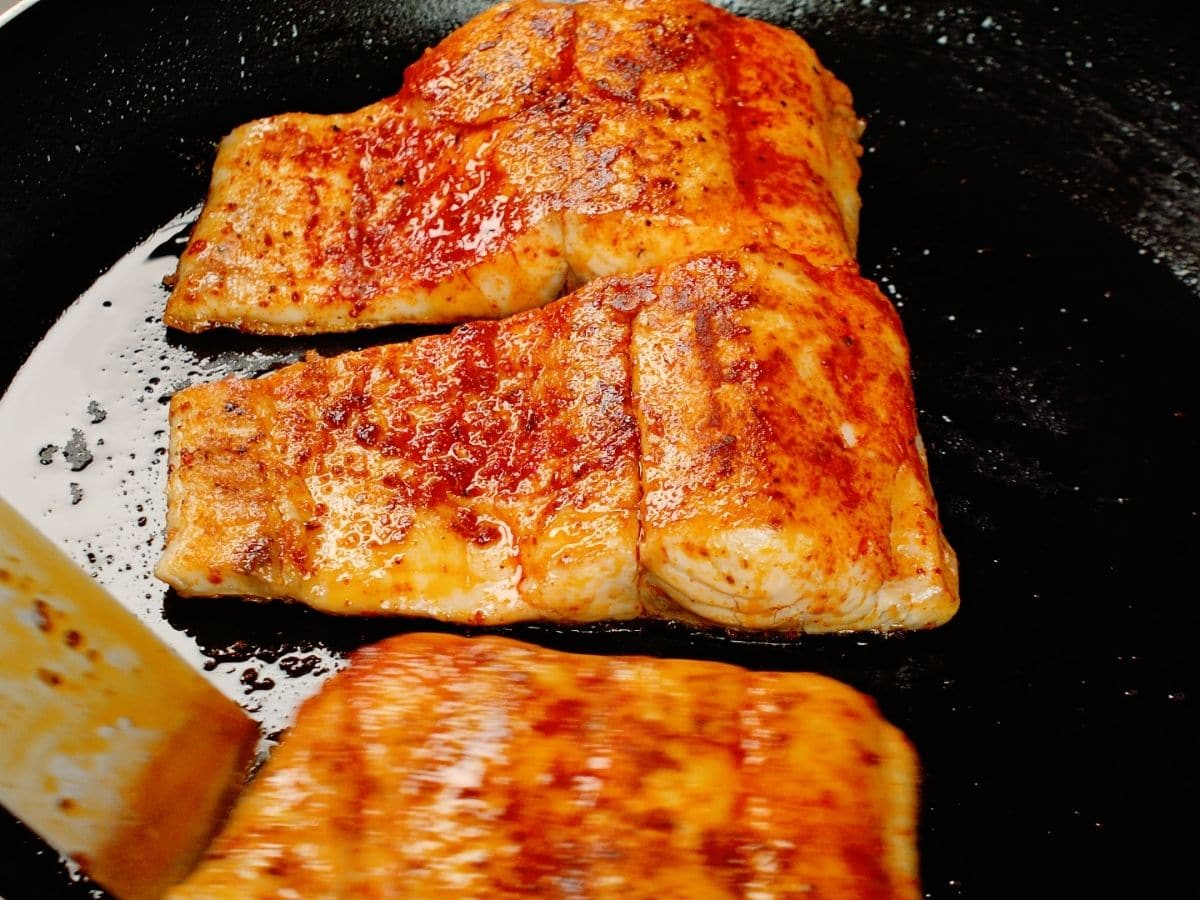 Three fish filets cooked in skillet