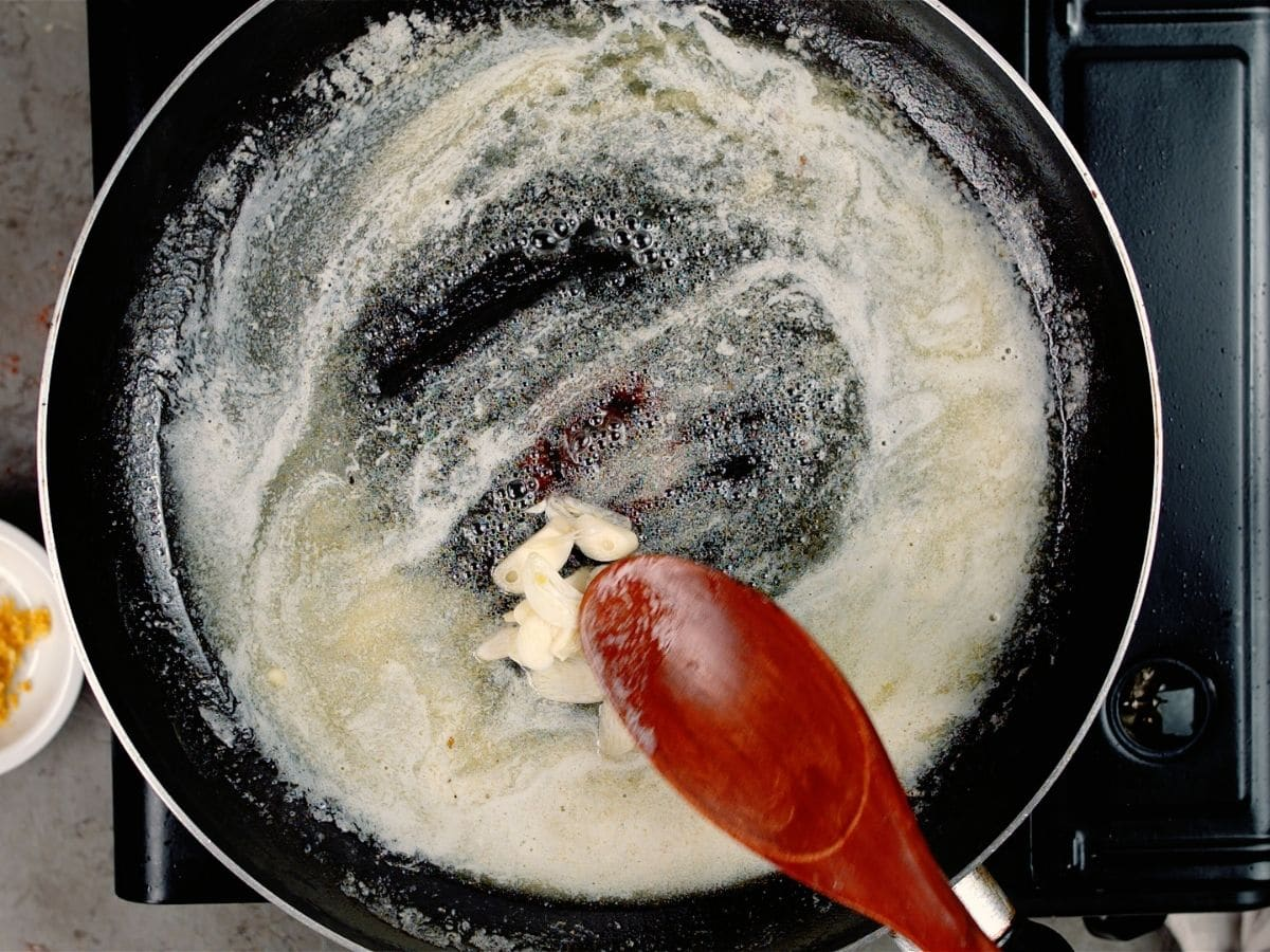wooden spoon stirring butter and garlic in skillet