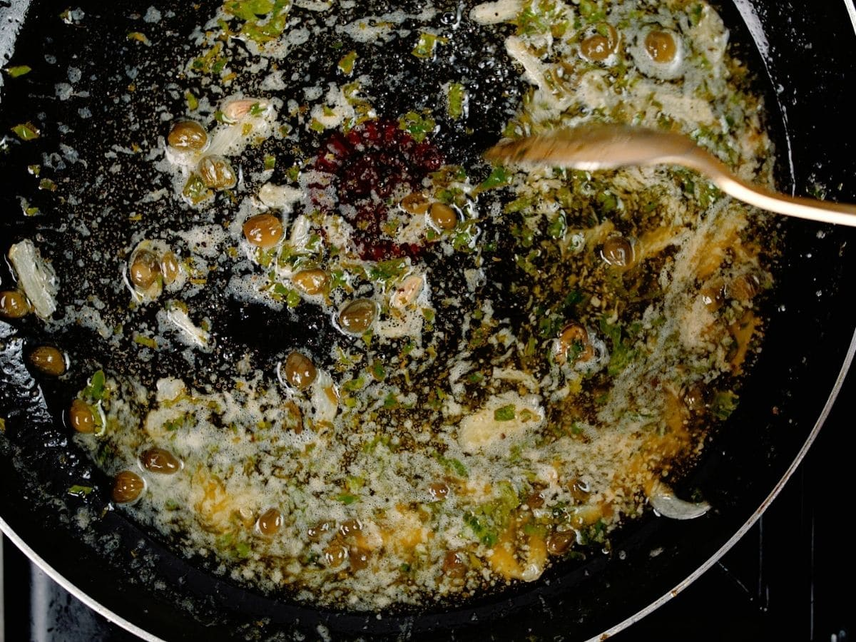 sauce with capers in black skillet