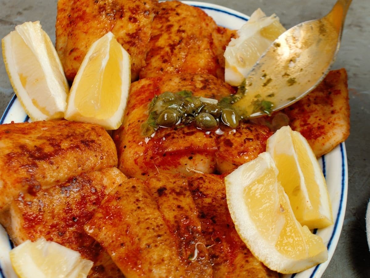 white plate topped with fish and lemon wedges