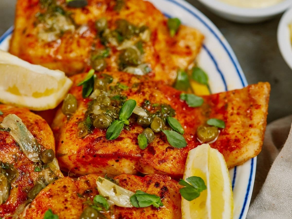 Fish filets with capers and herbs on plate