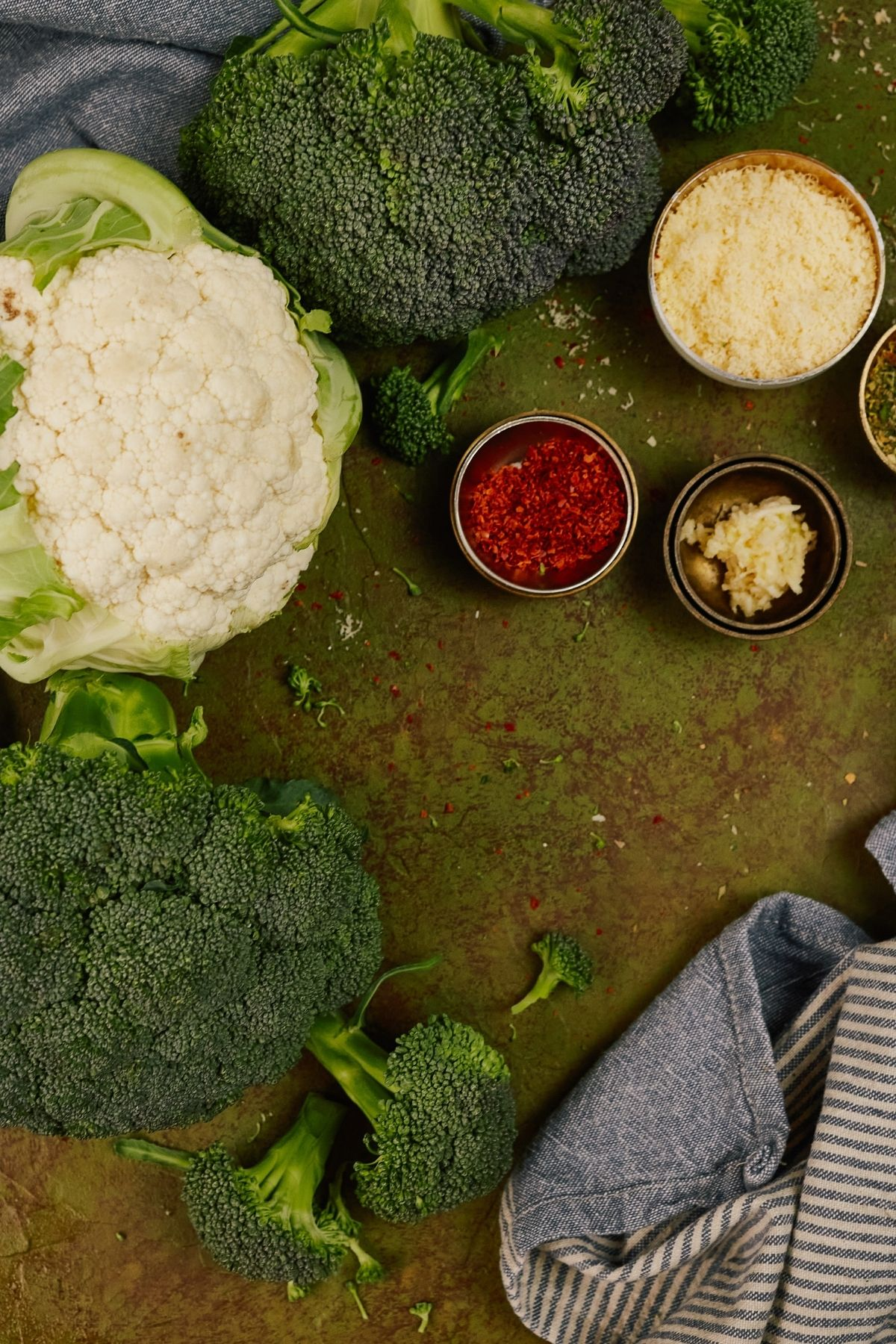 cauliflower and broccoli with bowls of spices on green table by gray napkin