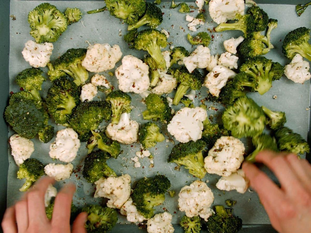 Hands tossing vegetables on baking sheet