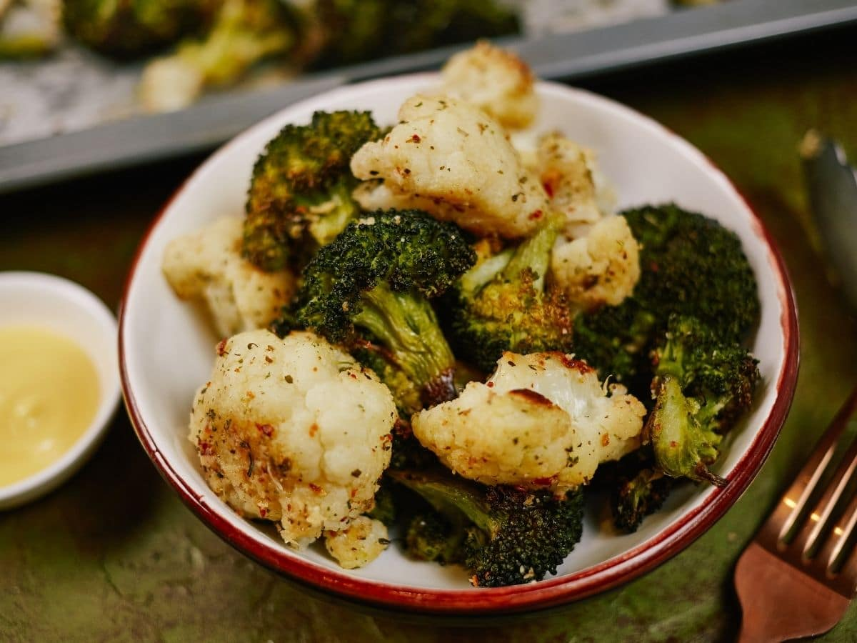white bowl of broccoli and cauliflower on green table