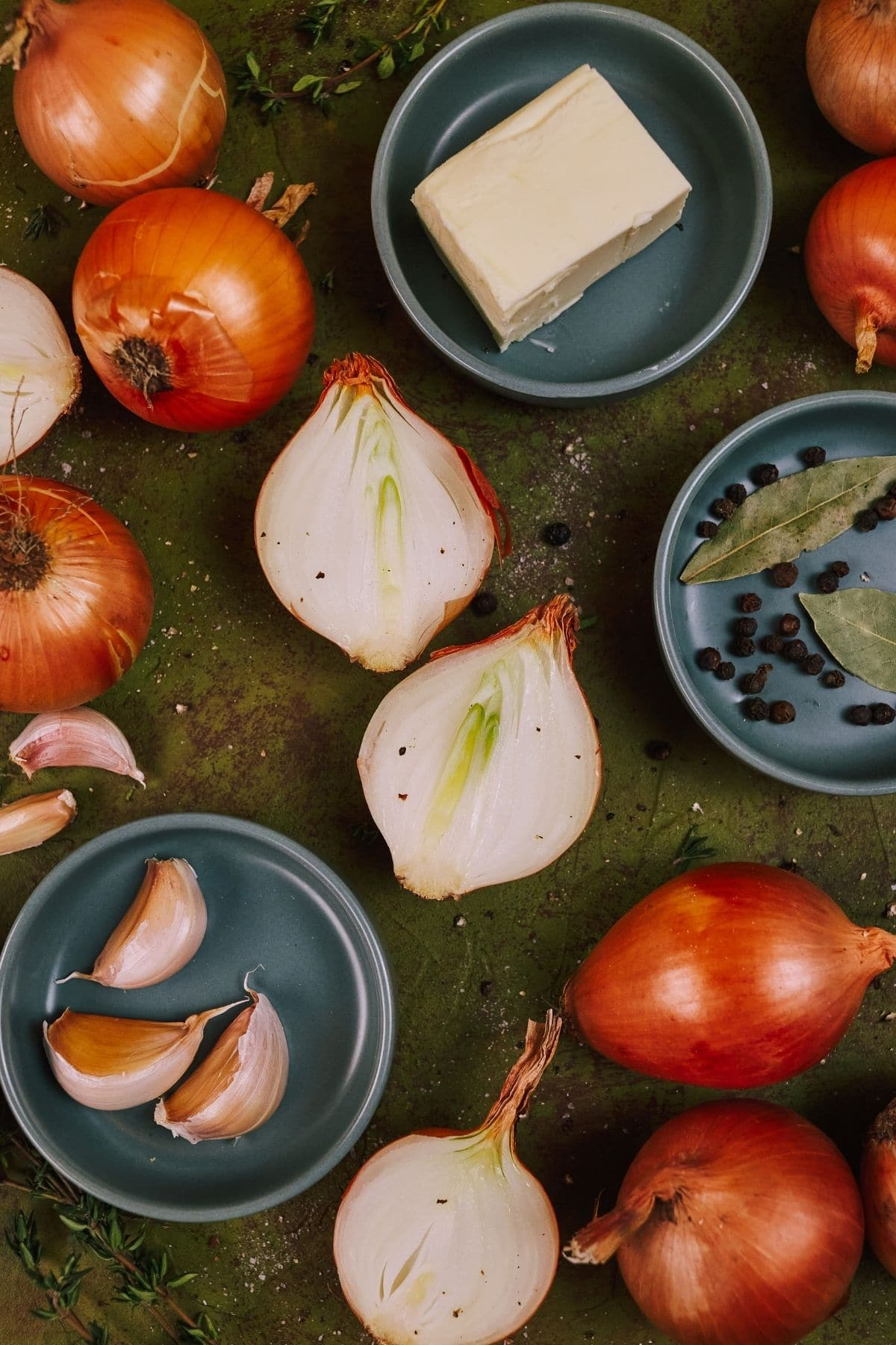 Onions on green table with teal bowls of spices and butter