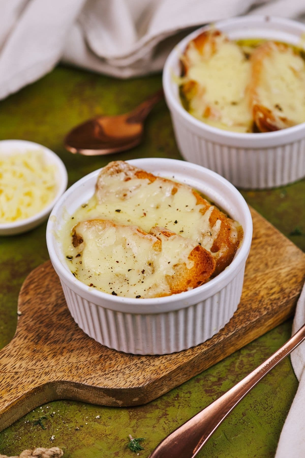 Two white ramkens of french onion soup on green tablecloth