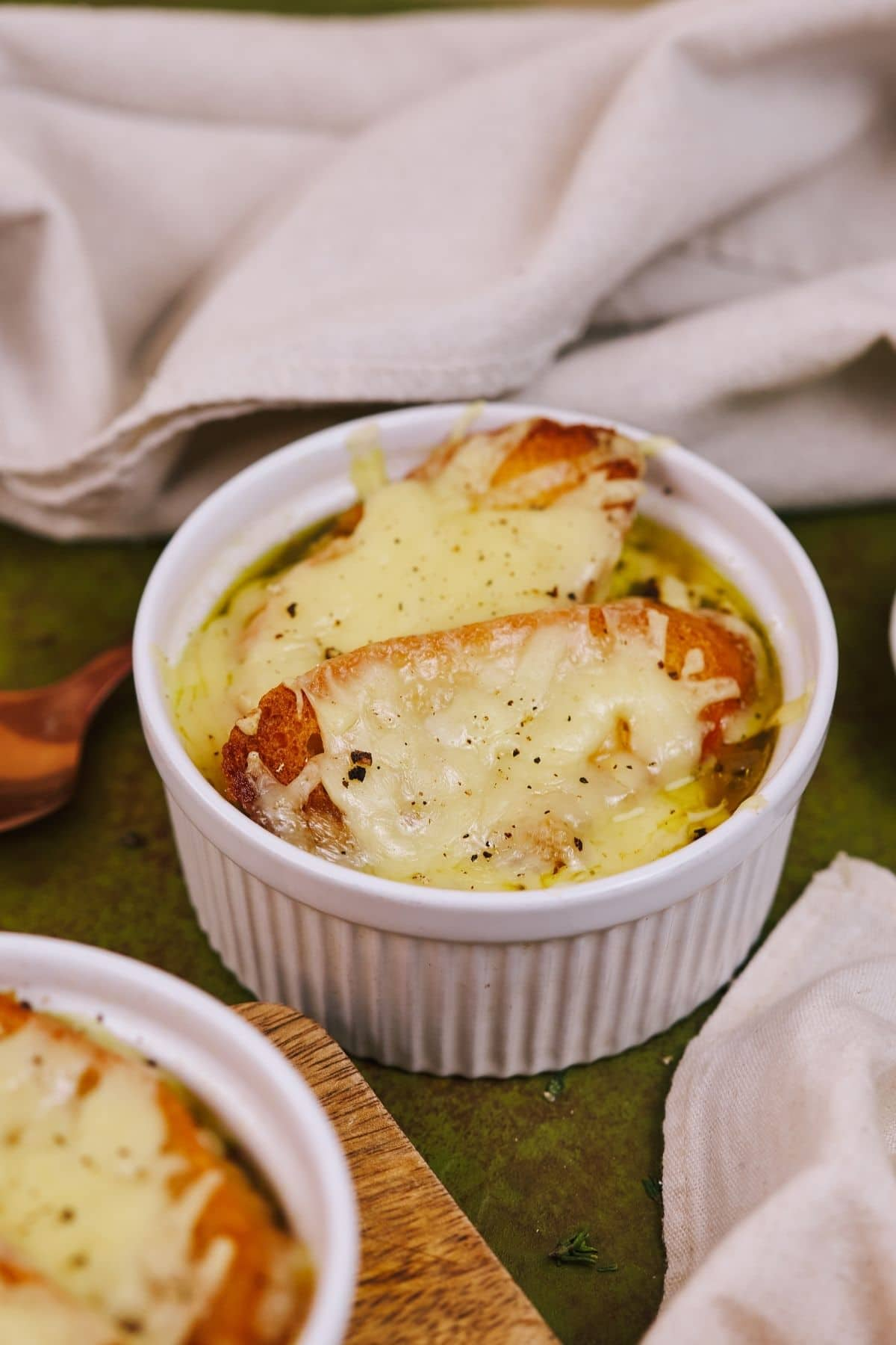 Ramekins on green table filled with french onion soup