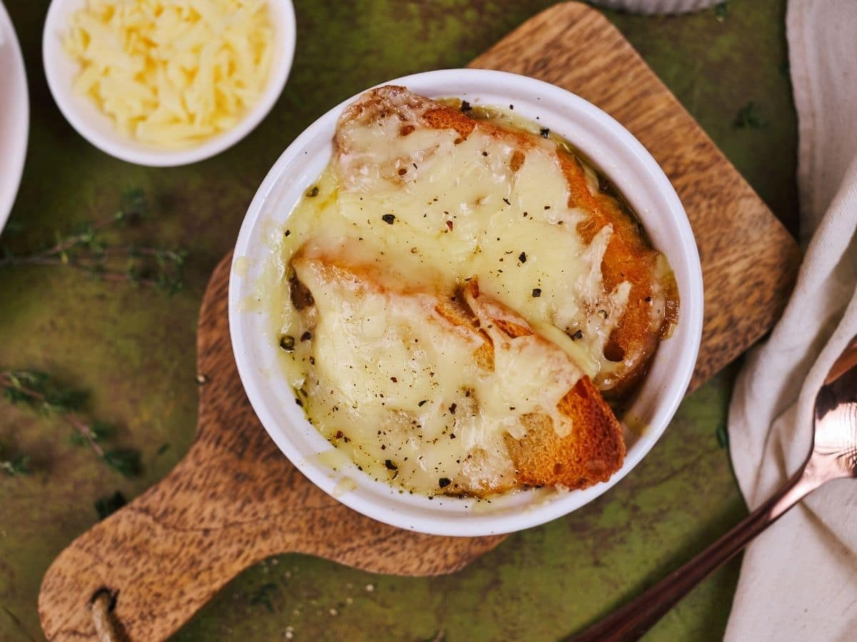 Melted cheese and toasted bread on top of white ramekin of onion soup