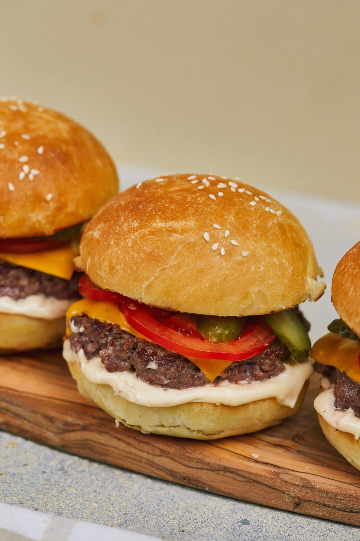 cheeseburger with sesame seed bun tomato and pickle on cutting board