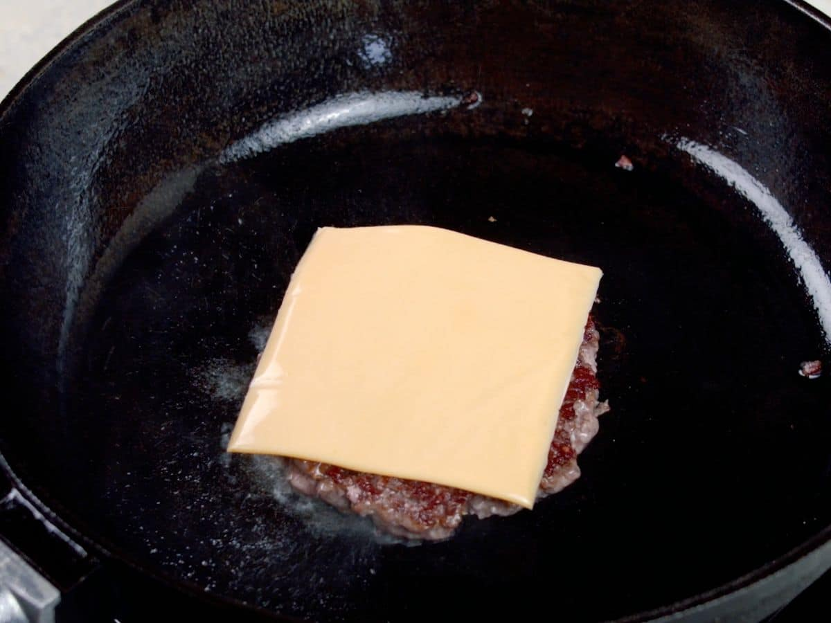 Hamburger in skillet topped with cheese