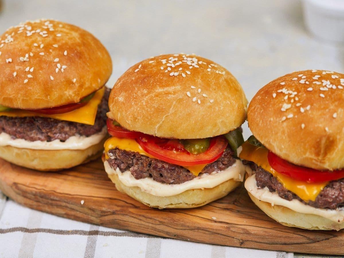 Three hamburgers with sesame buns sitting on cutting board that's on striped napkin