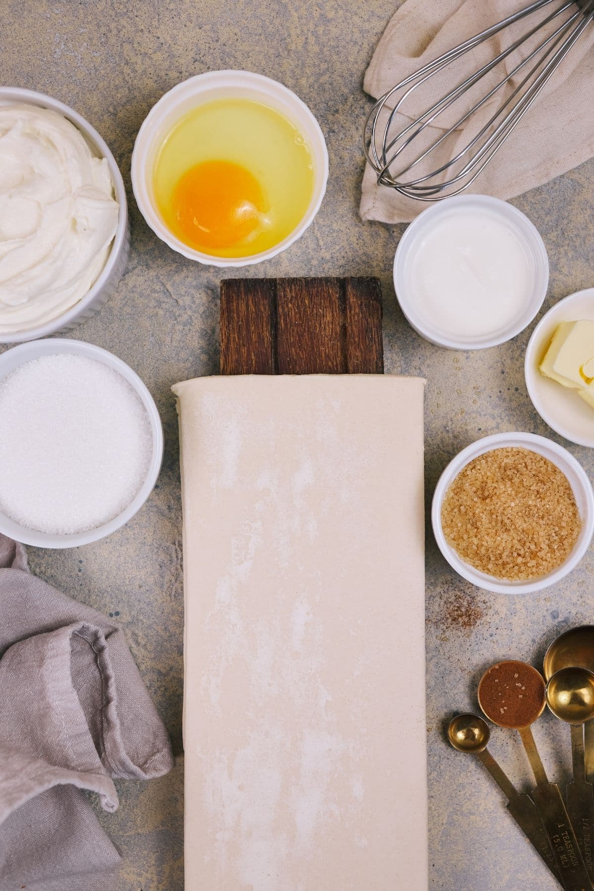 Puff pastry on table with white bowls of cream cheese eggs and sugar