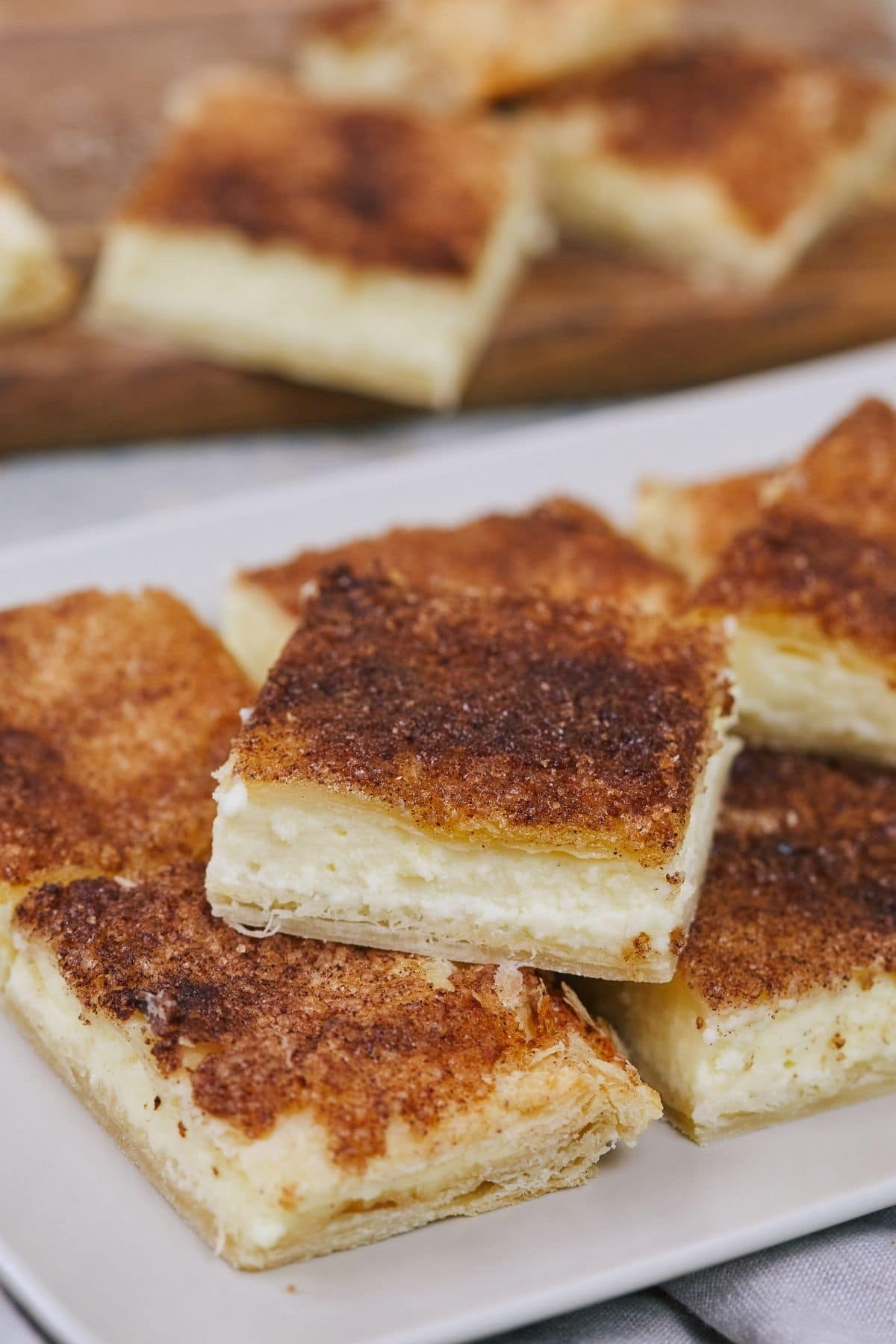 Cheesecake bars on white platter and wooden board