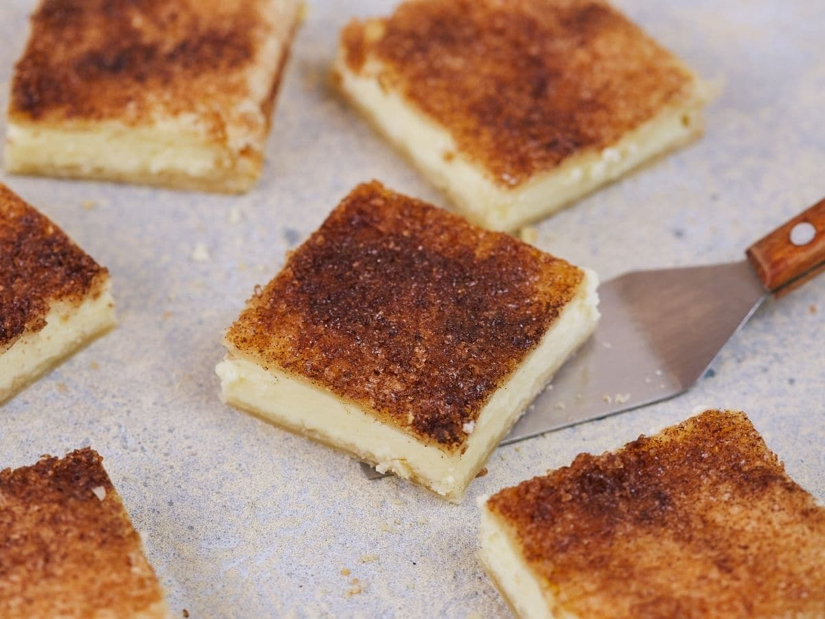 Image looking down on parchment paper holding six squares of cheesecake and spatula