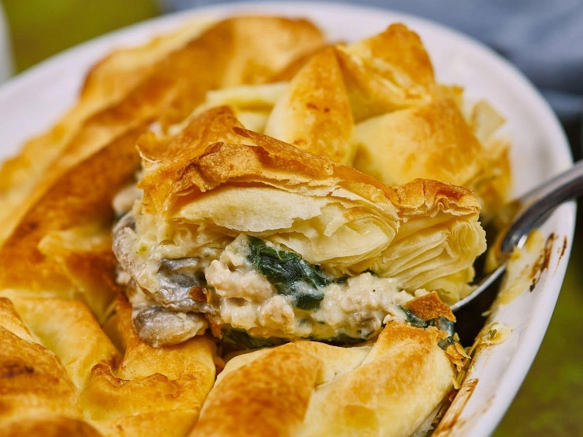 piece of spanakopita being lifted out of baking dish to serve