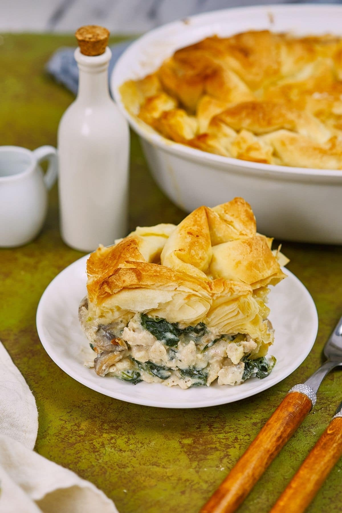 Greek spanakopita on white saucer next to wooden spoon and fork