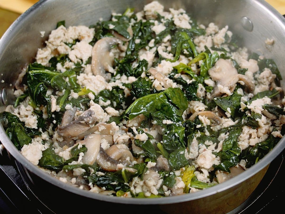 spinach in skillet with ground meat and mushrooms