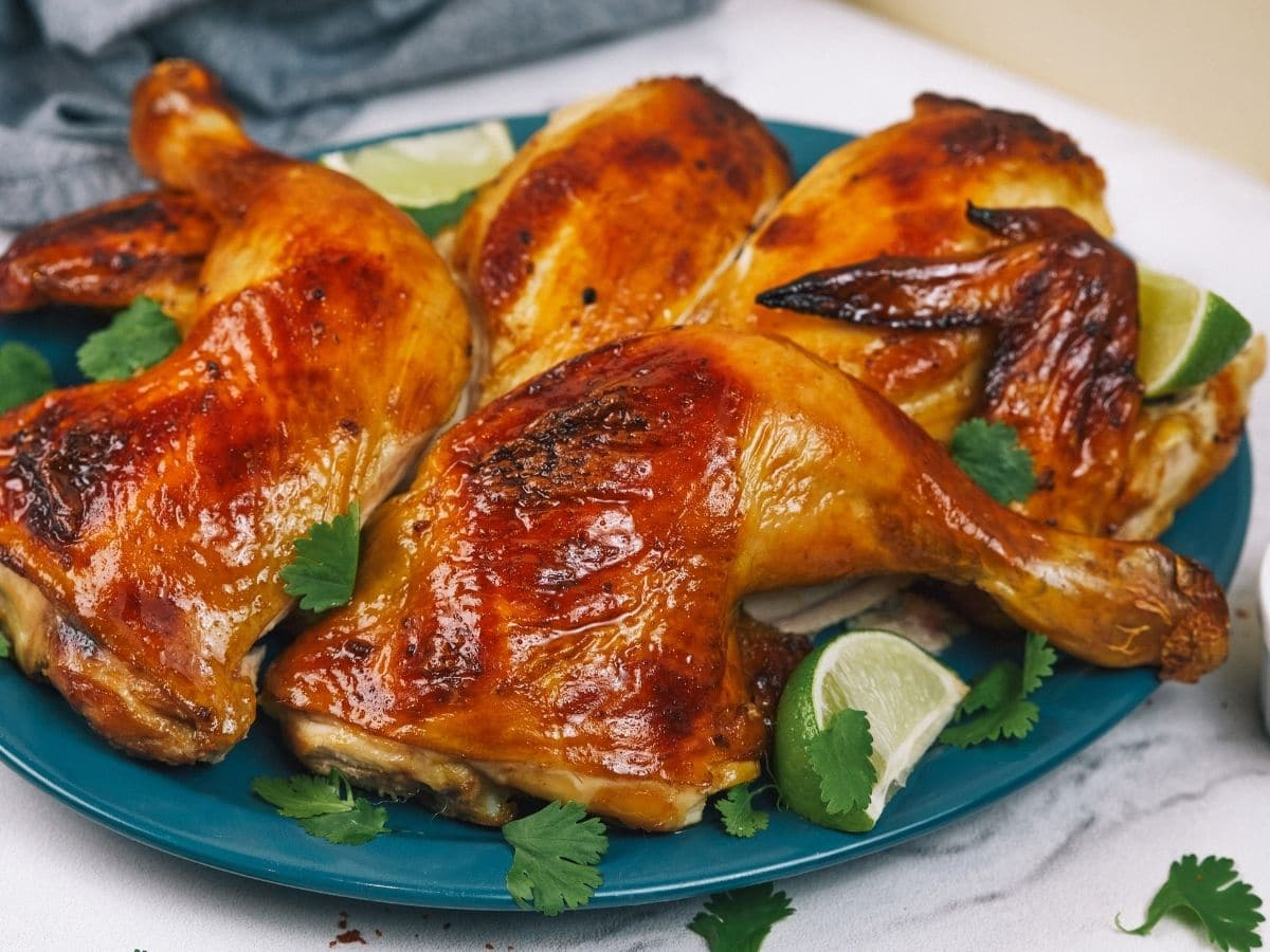 Teal platter of roasted chicken on white table