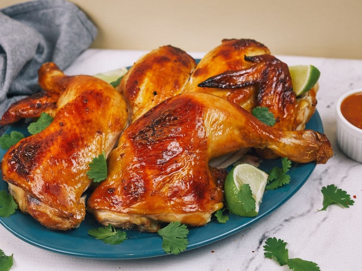 Baked chicken legs on blue plate next to blue napkin on white table
