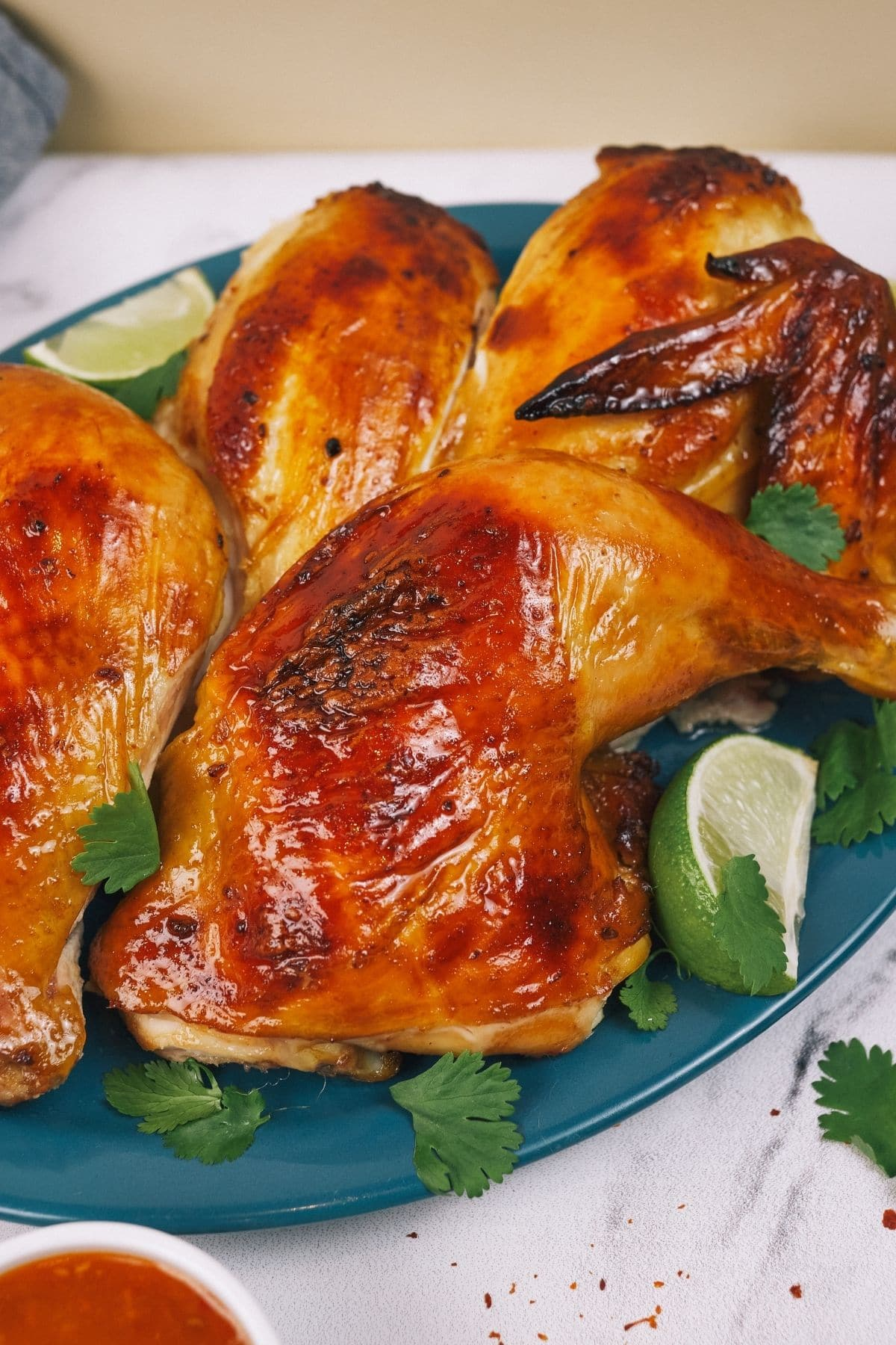 Roasted chicken leg quarters on teal plate with lime wedges