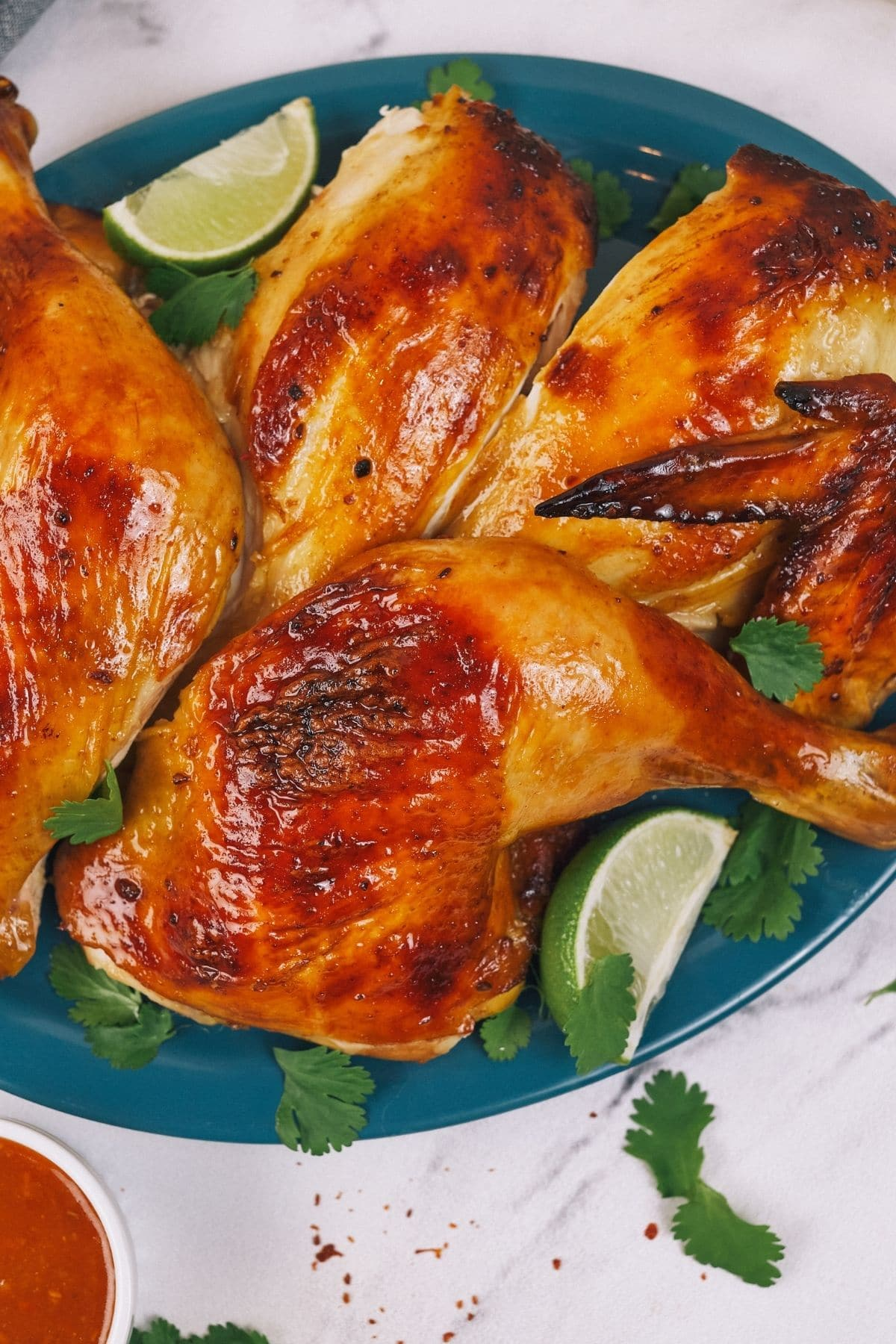 Roasted chicken on teal plate with lime wedge on white table