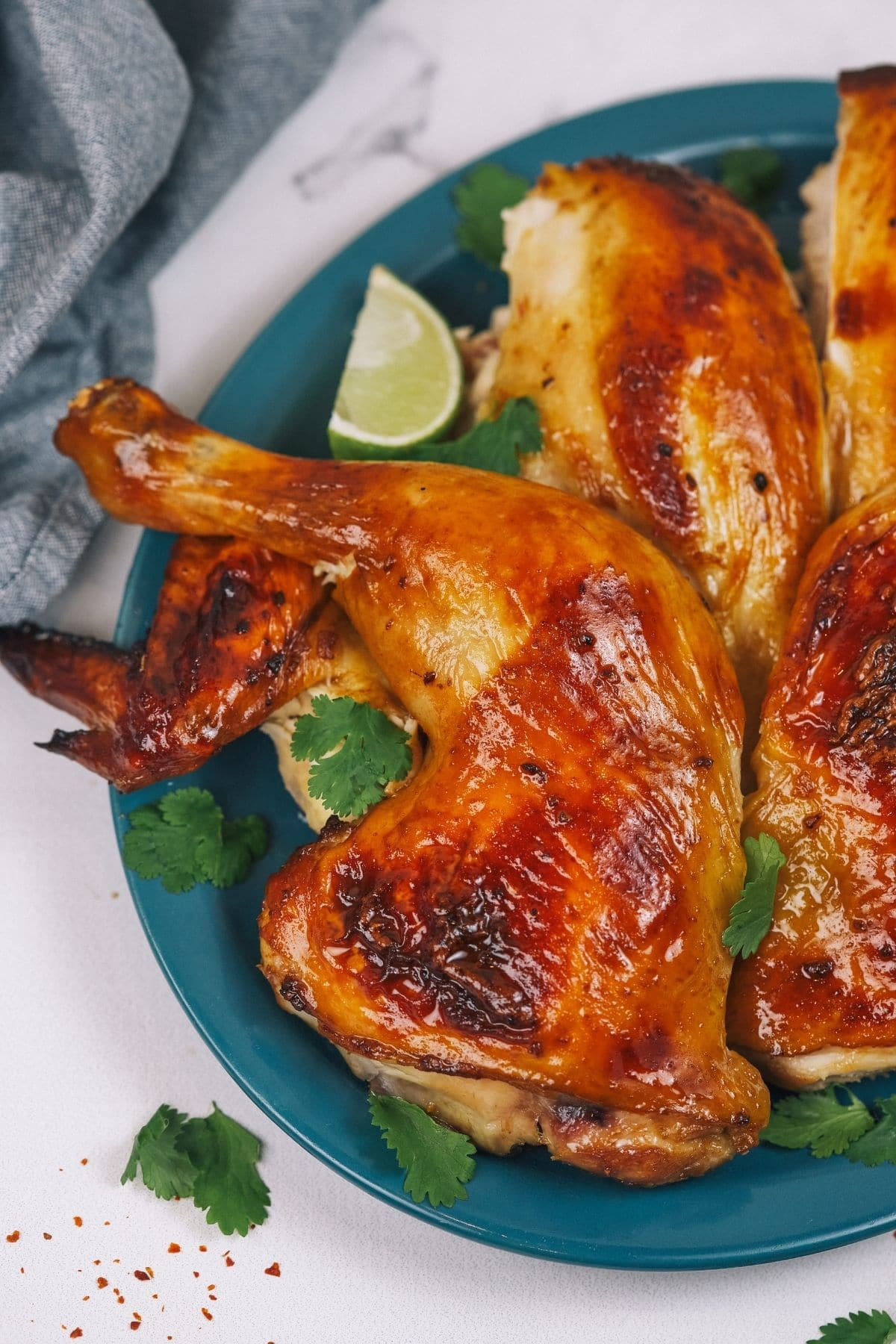 Teal plate of roasted chicken next to blue cloth napkin