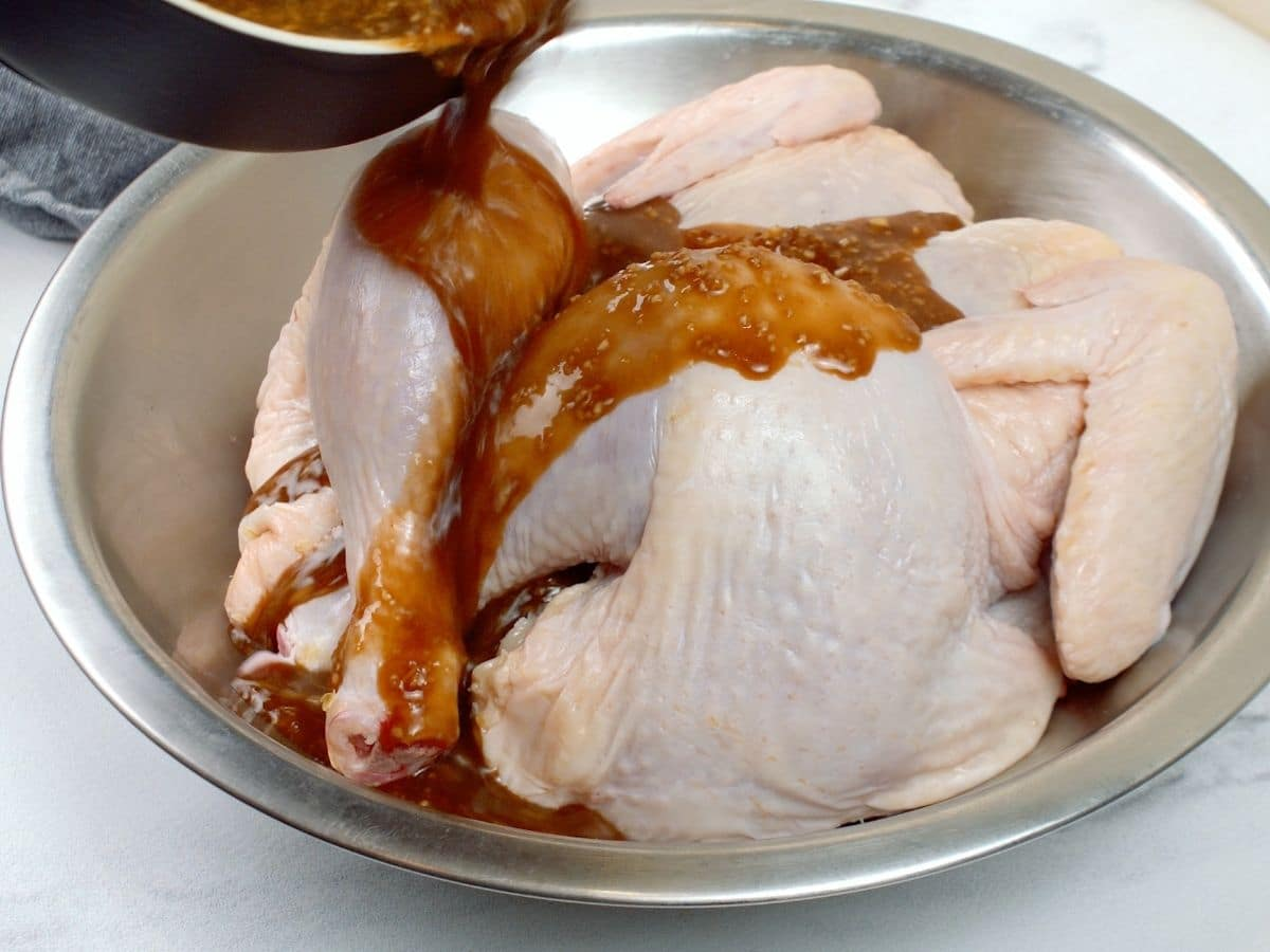 Bowl of sauce being poured over raw whole chicken