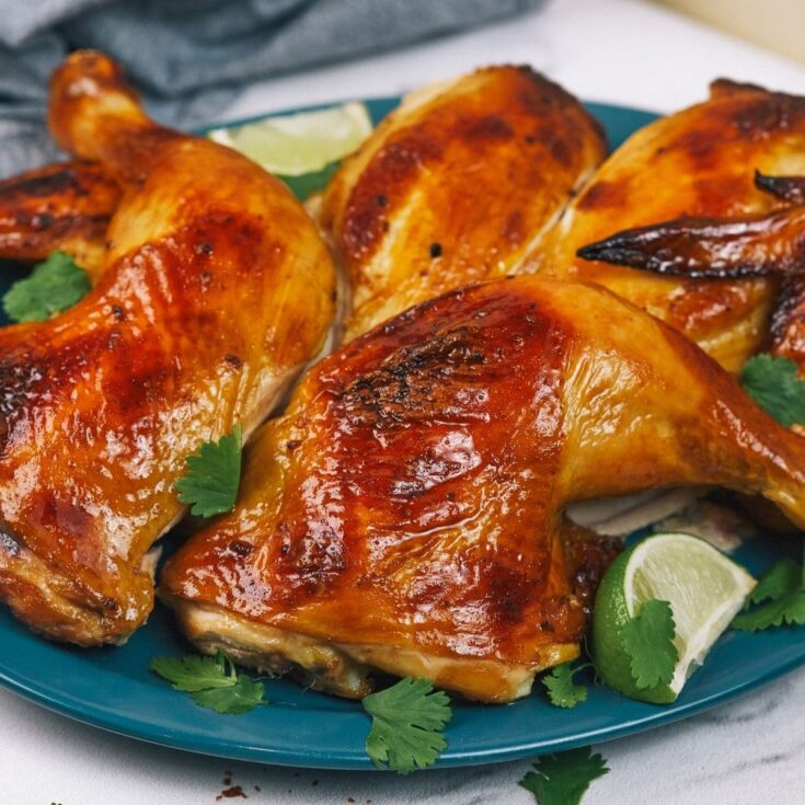 Teal plate holding roasted chicken with cilantro and lime wedges