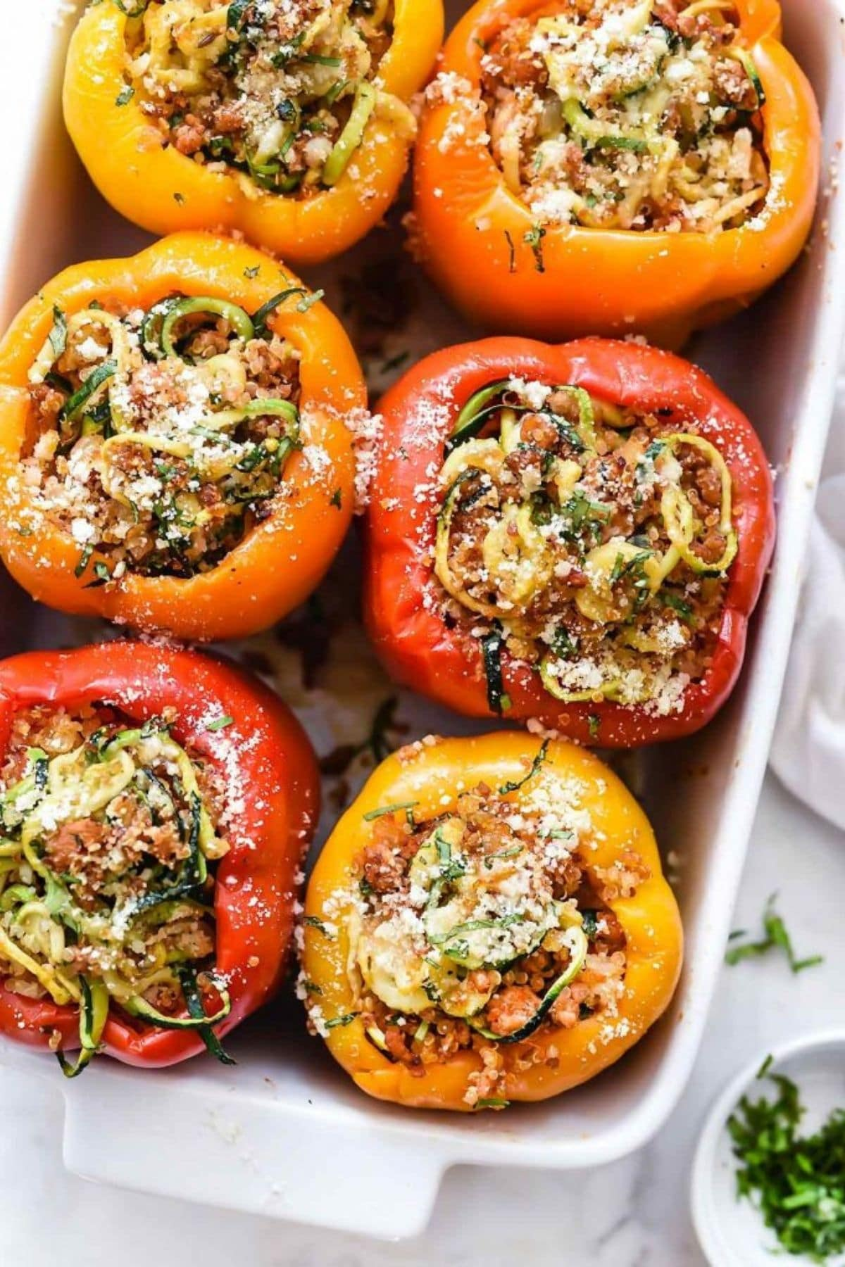 White baking dish filled with stuffed bell peppers