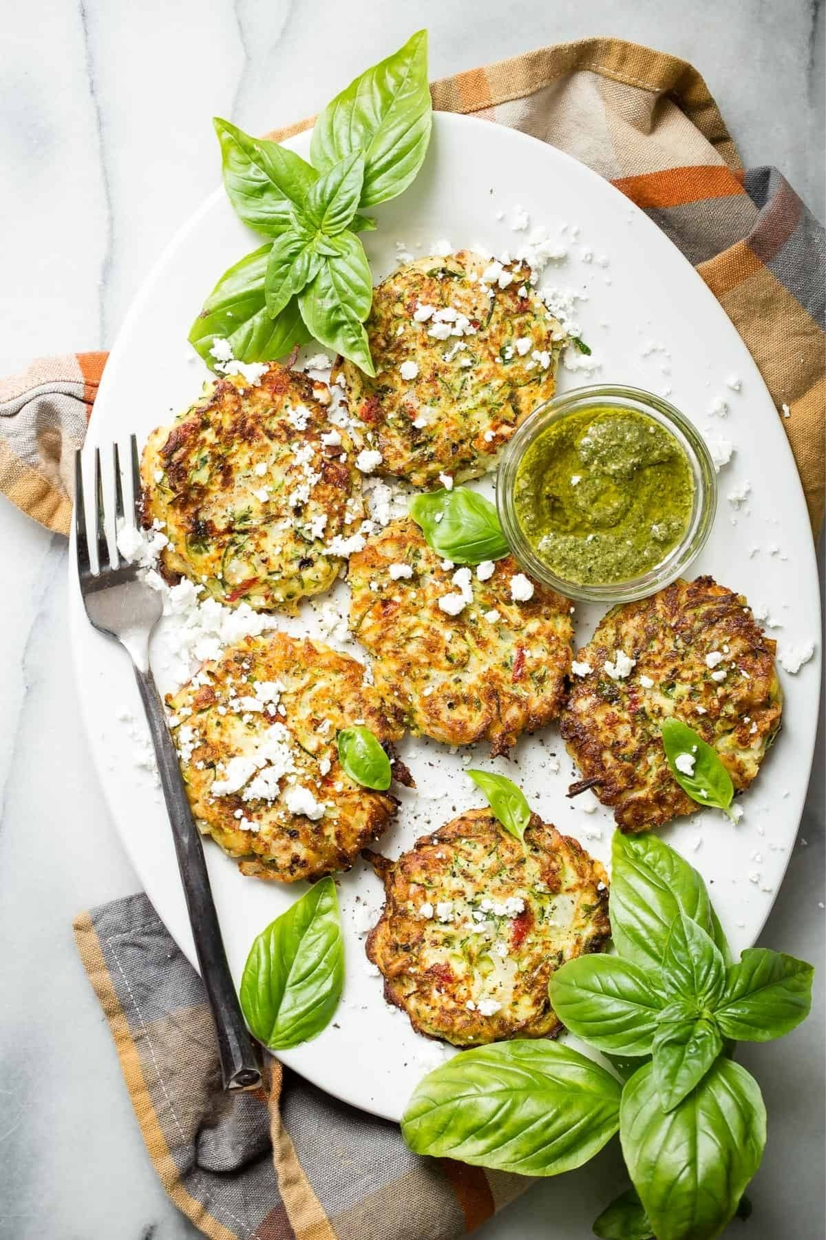 White platter of fritters with large basil leaves on top