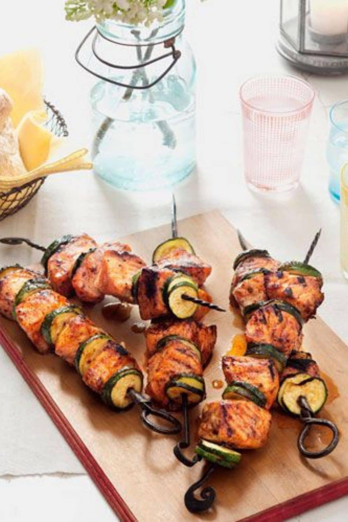 Salmon and zucchini skewers on cutting board