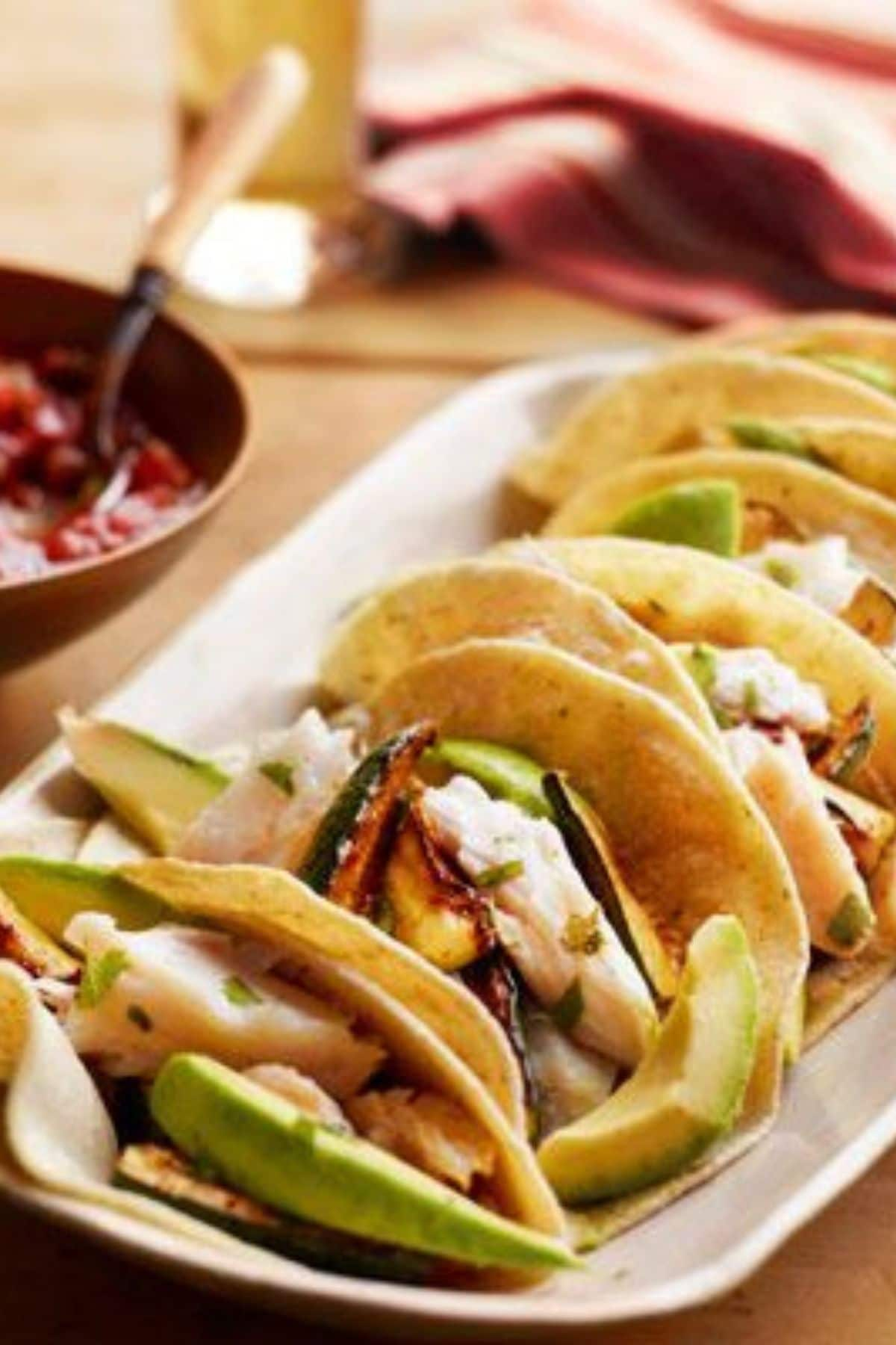 Fish tacos with avocado on white platter