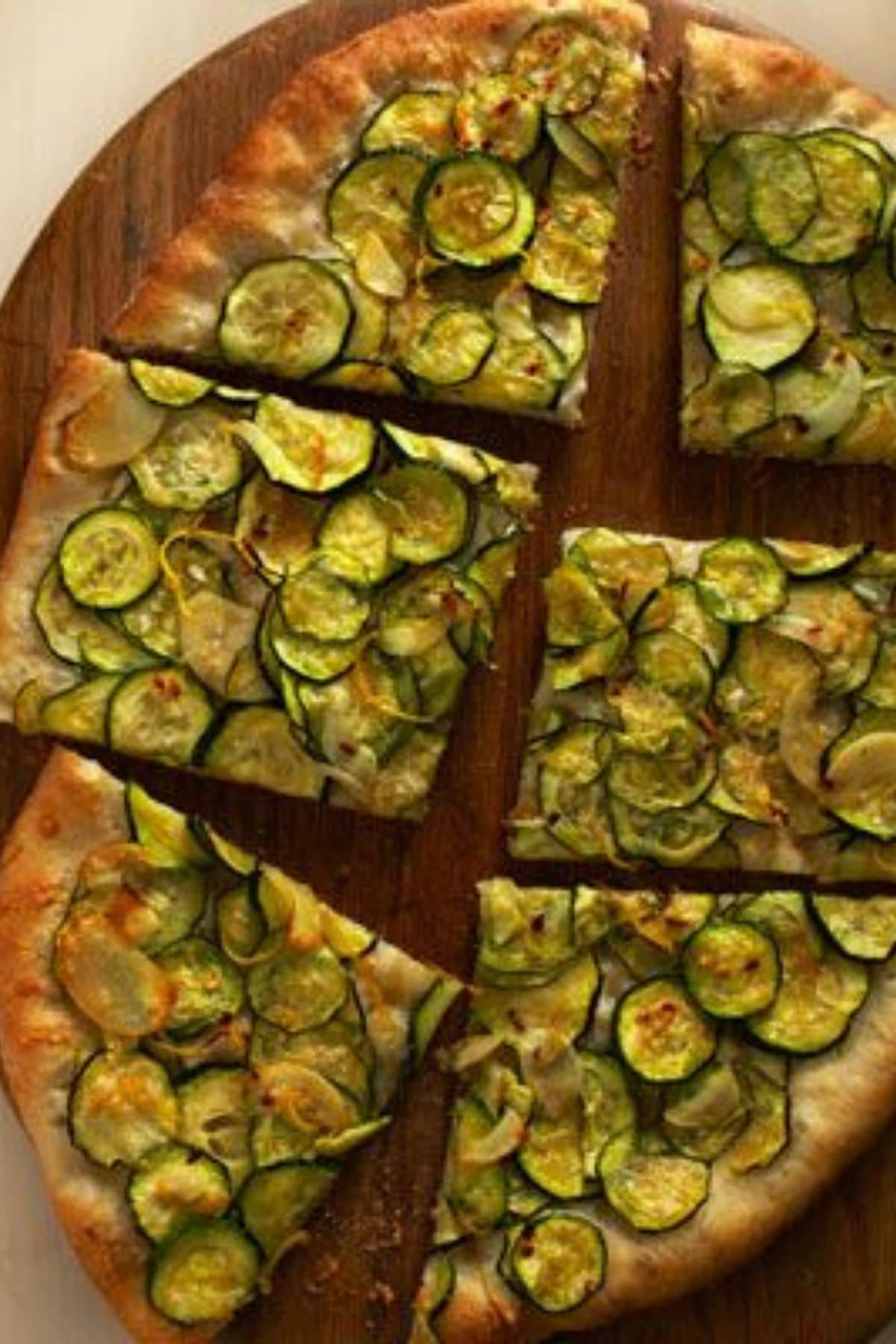 Pizza on cutting board topped with zucchini