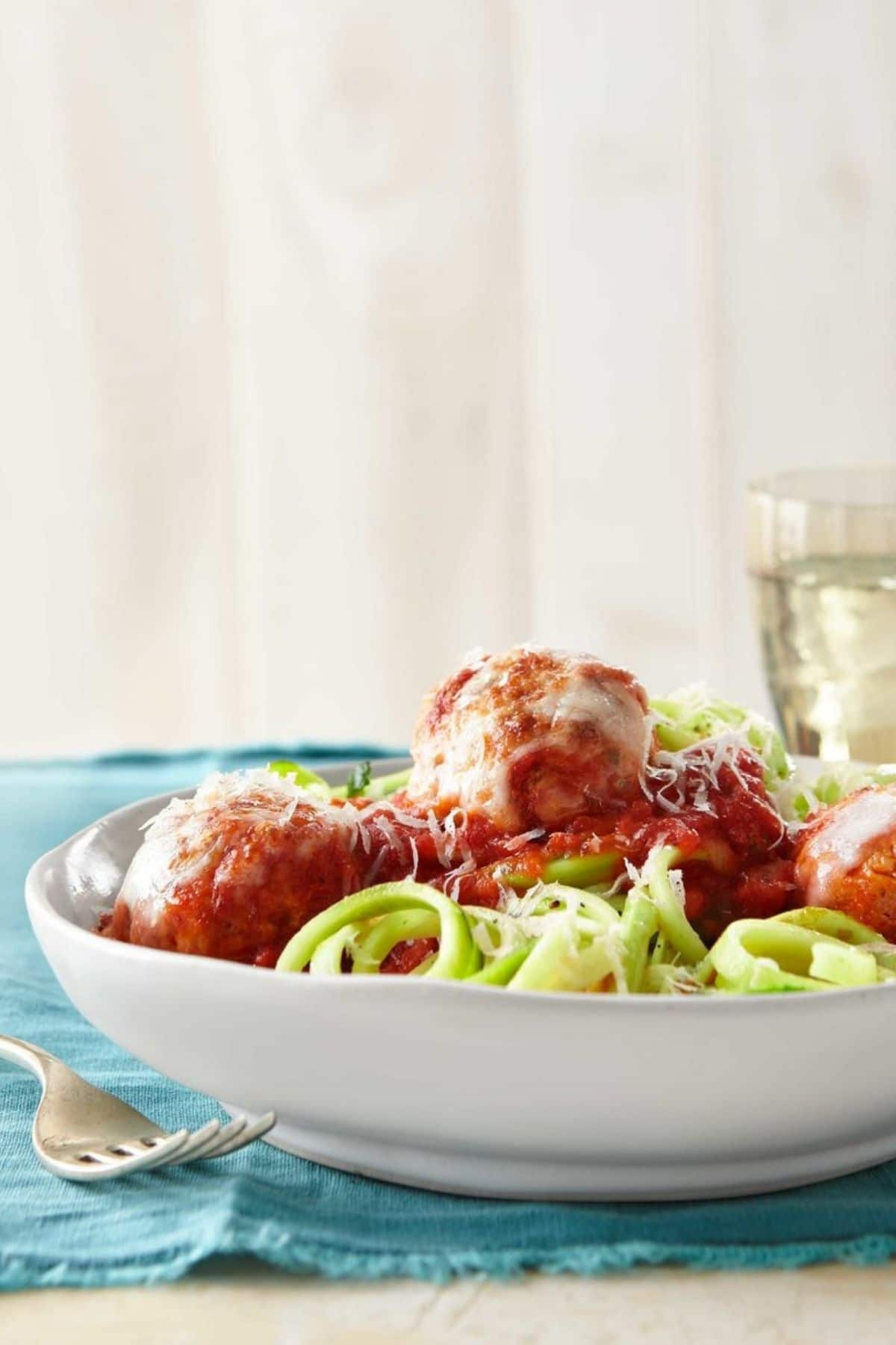 White bowl of zucchini pasta and meatballs on blue cloth napkin