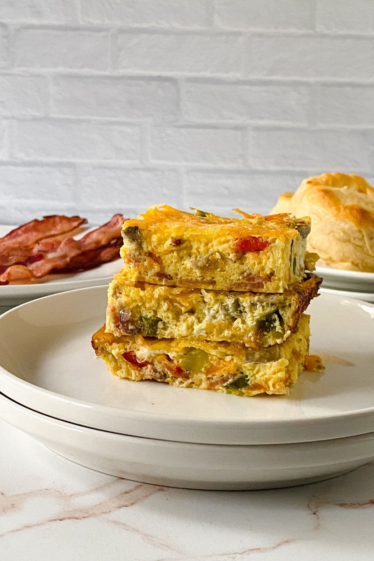 sliced egg bake with bacon and biscuits on plates in background