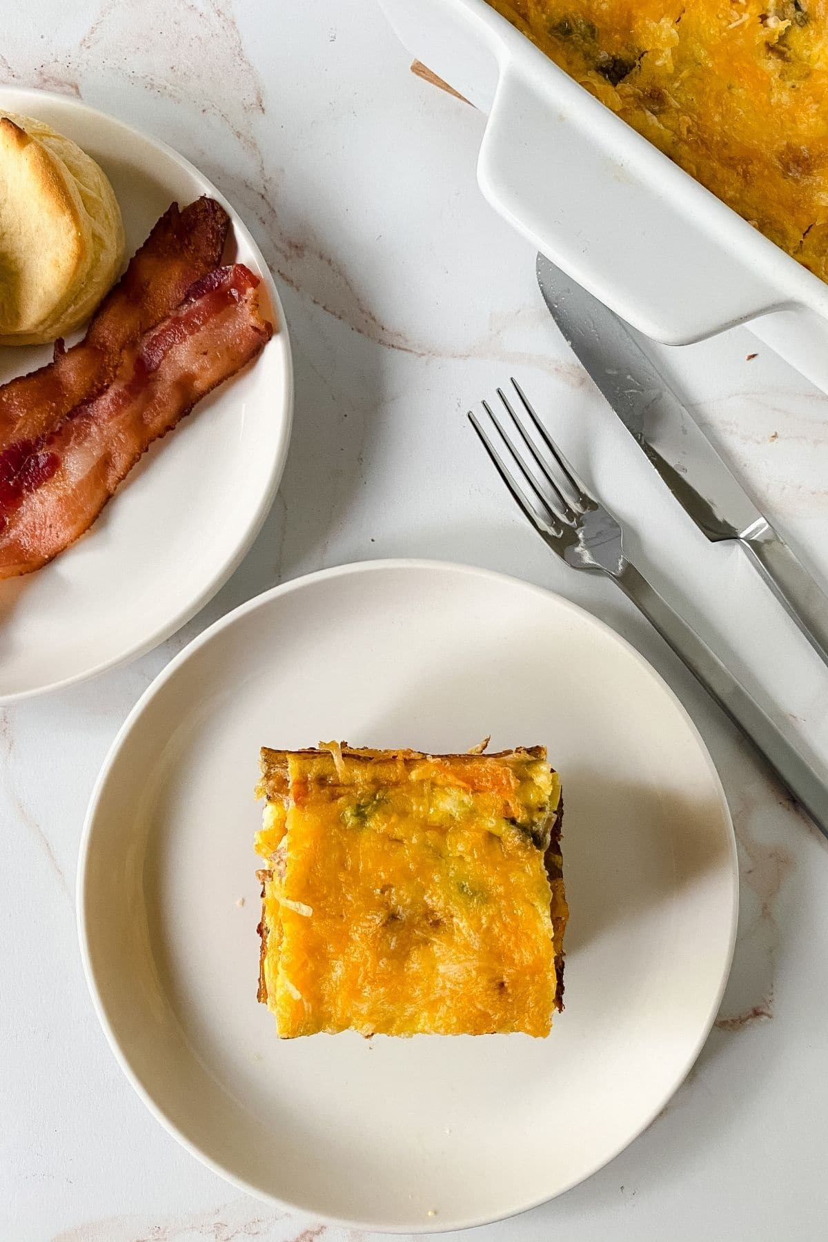image looking down on white with square egg bake next to silverware on marble