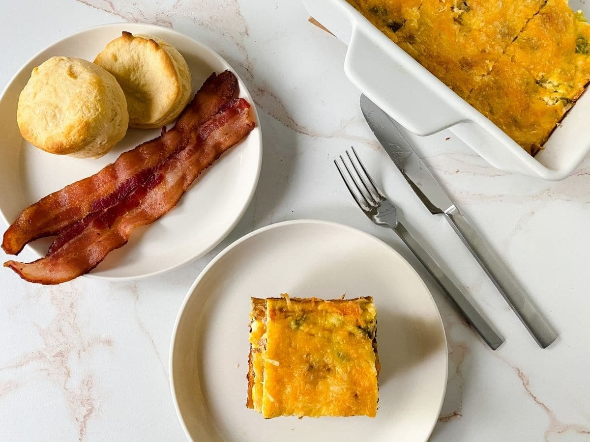 two white plates on table one with bacon and biscuit and one with frittata